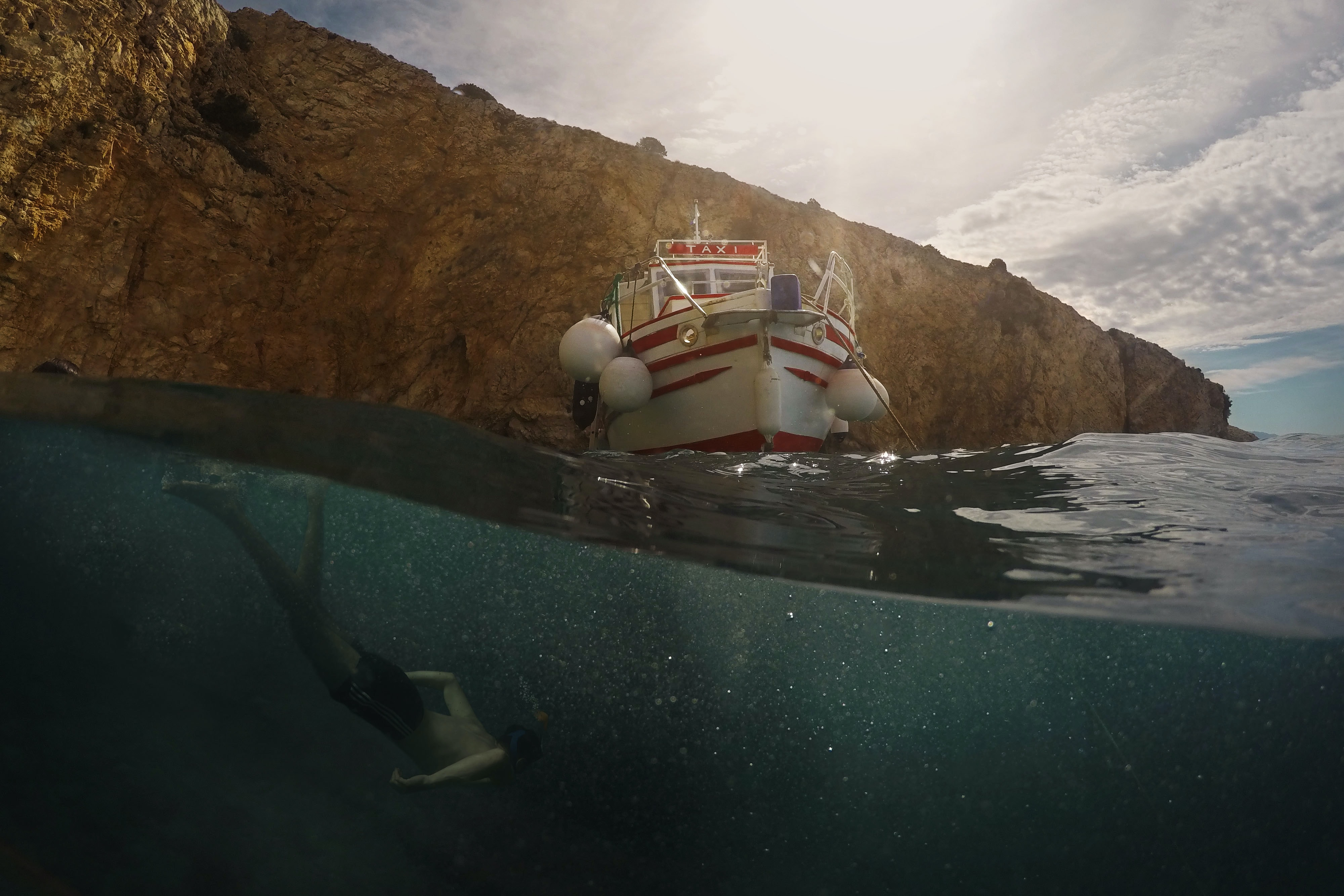 An impressive shot of a man diving near a water taxi by a cliff