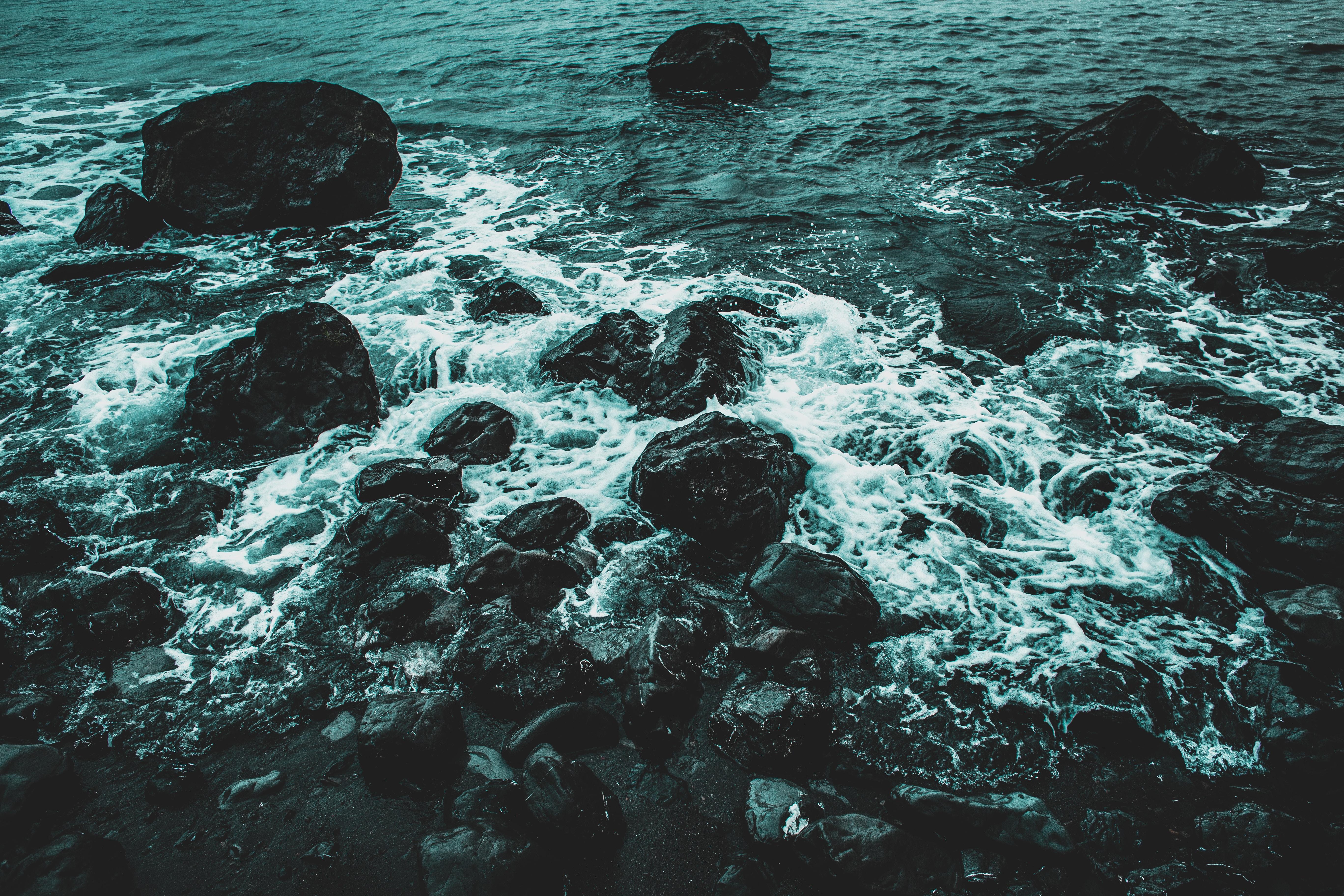 Dark rippling waves hitting into rocks.
