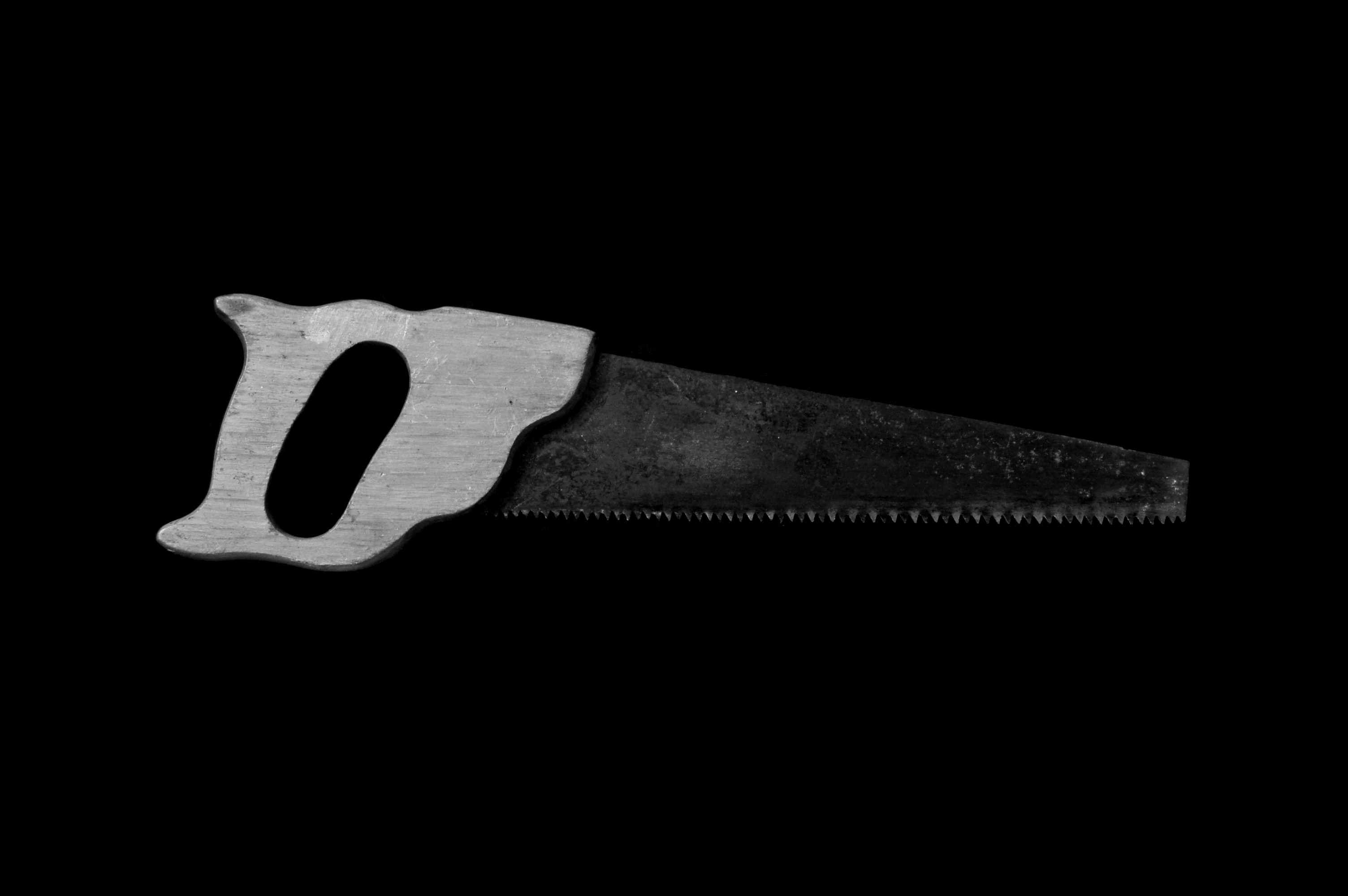grayscale photo handsaw