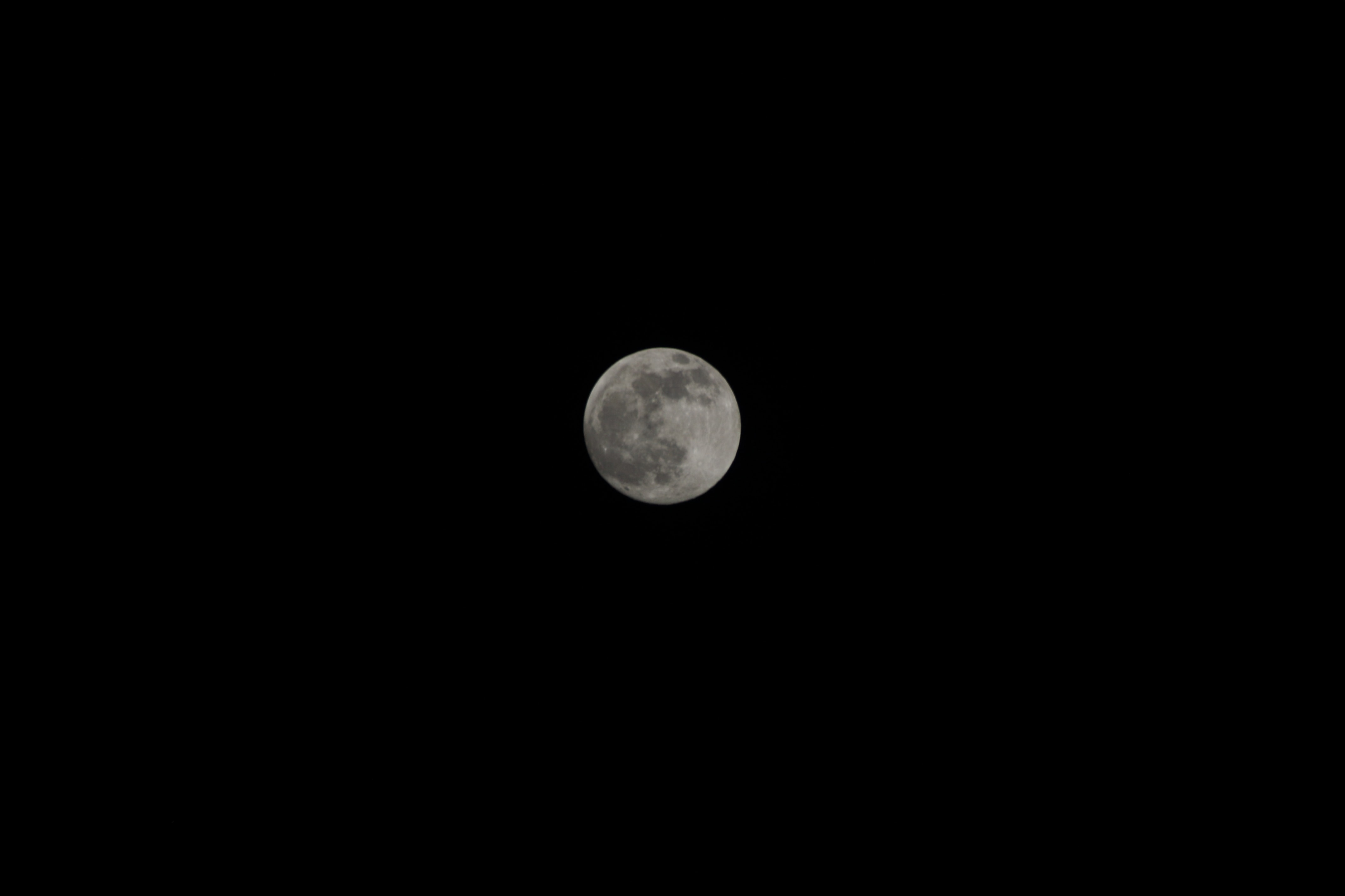 Full moon with visible dark spots against a black night sky in Caracas