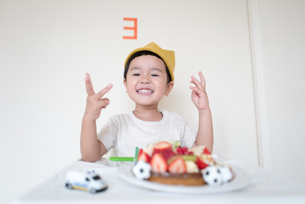 boy in front of cake and white car toy