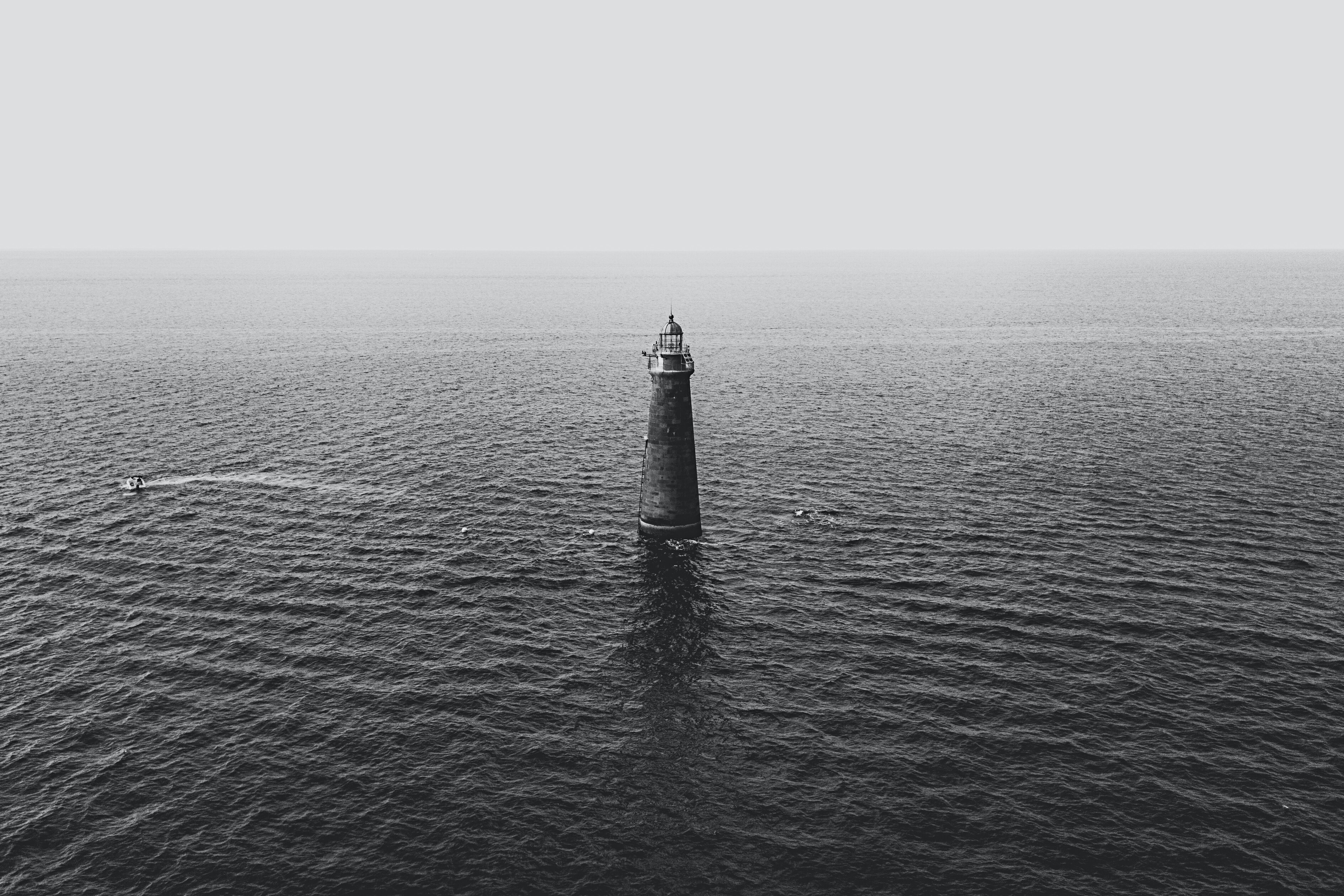 gray concrete lighthouse surrounded by ocean water
