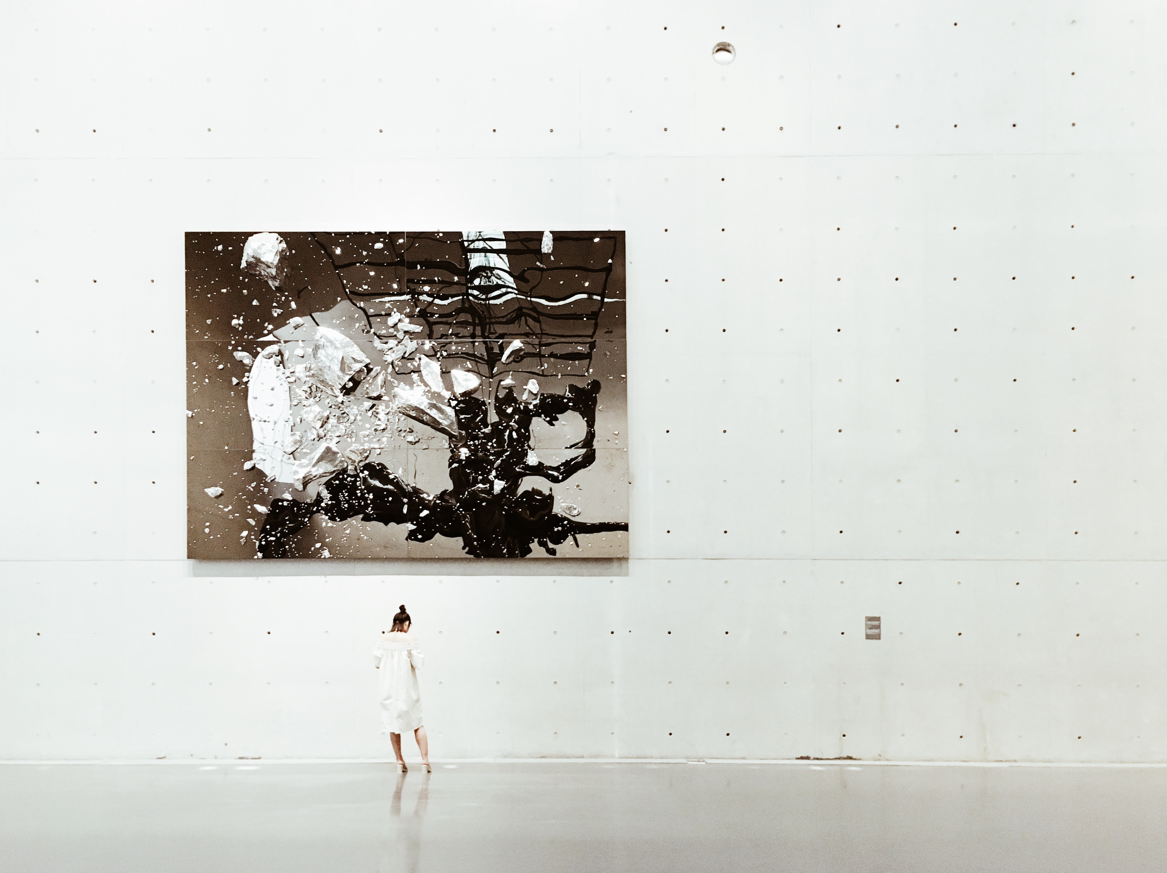 A woman standing near a painting in a modern art gallery