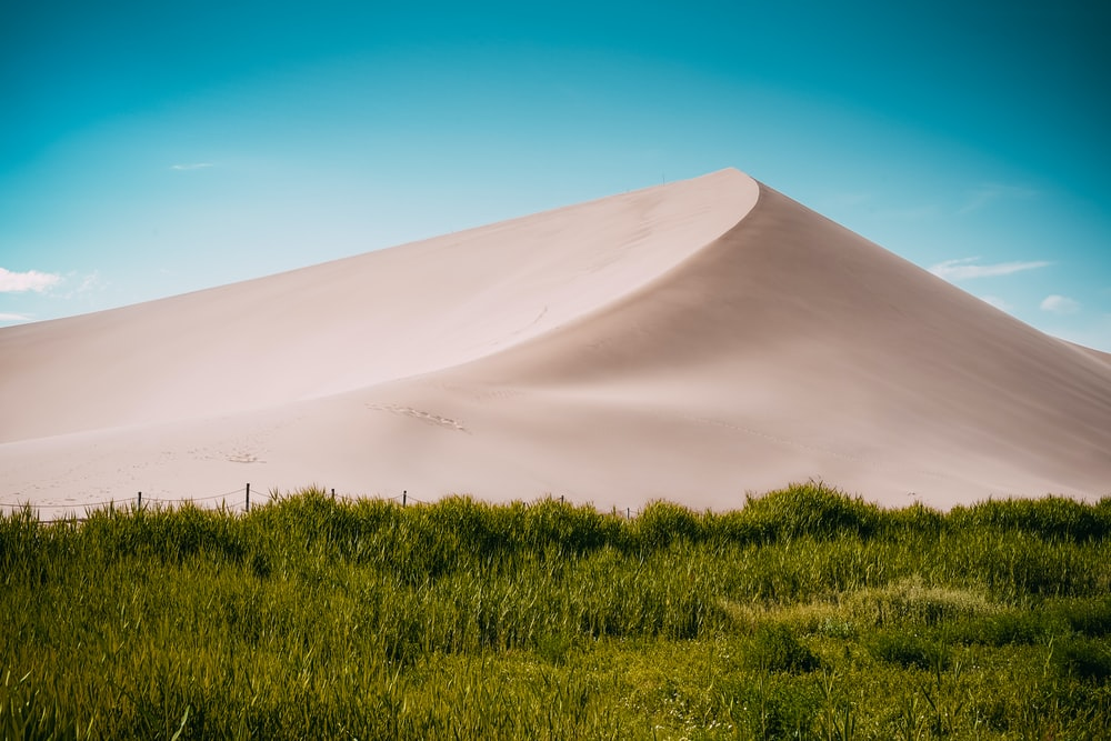 desert mountain near green field