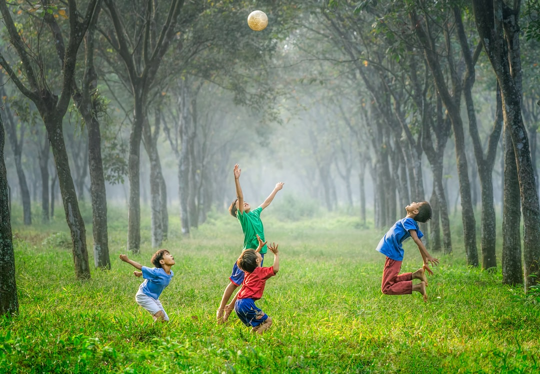 Soccer ball in the air, in the woods with children jumping - Is soccer a sport or an activity?