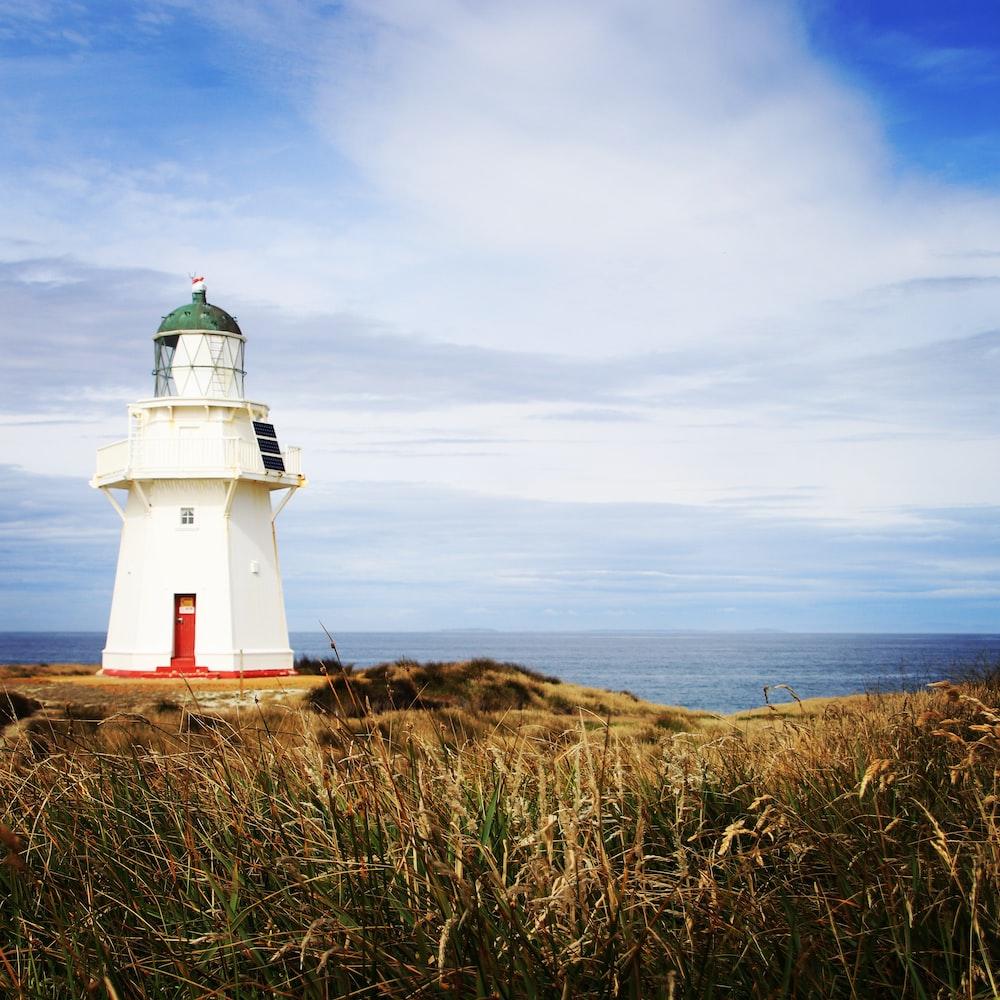 photo of white concrete lighthouse near ocean under blue cloudy sky