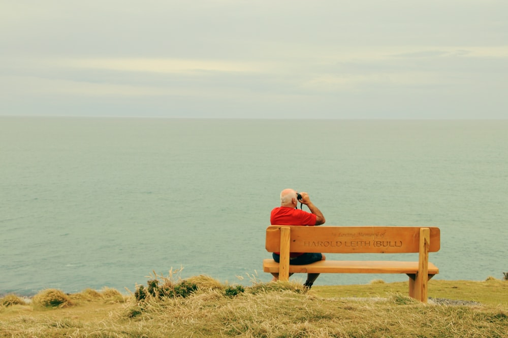 man wearing red t-shirt sitting on brown wooden bench facing on body of water