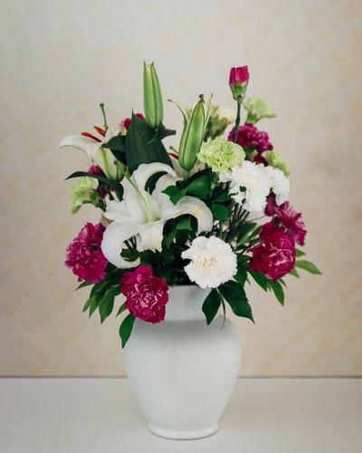 white and purple petaled flower arrangement on white vase