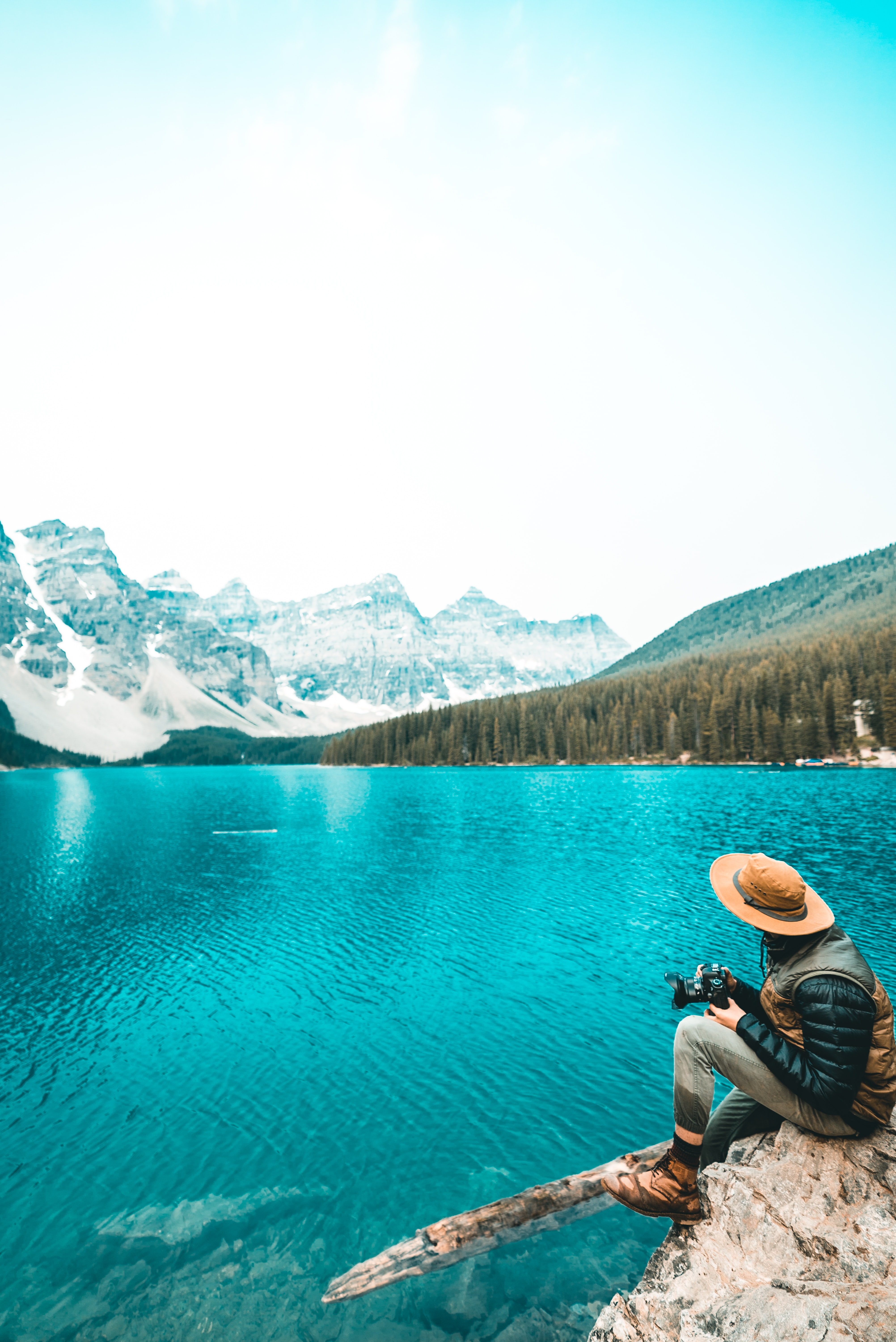 A person sitting on a rock over an azure lake and holding a camera