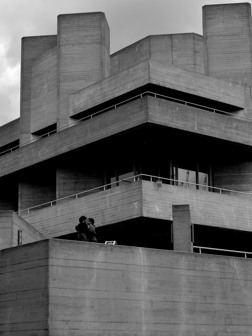 grayscale photography of two couple kissing on top of building
