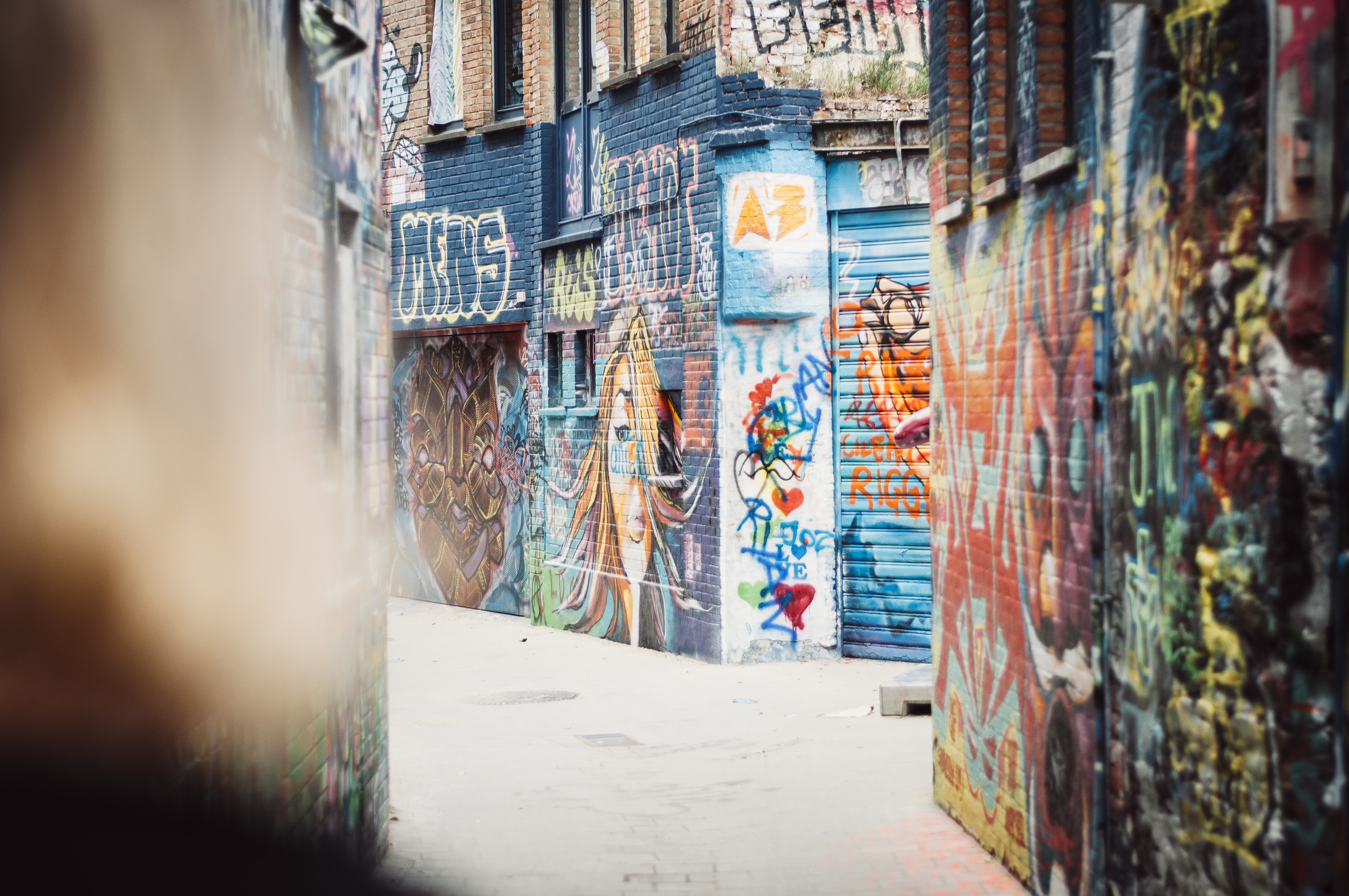 An empty alley in Ghent with its walls covered in colorful graffiti