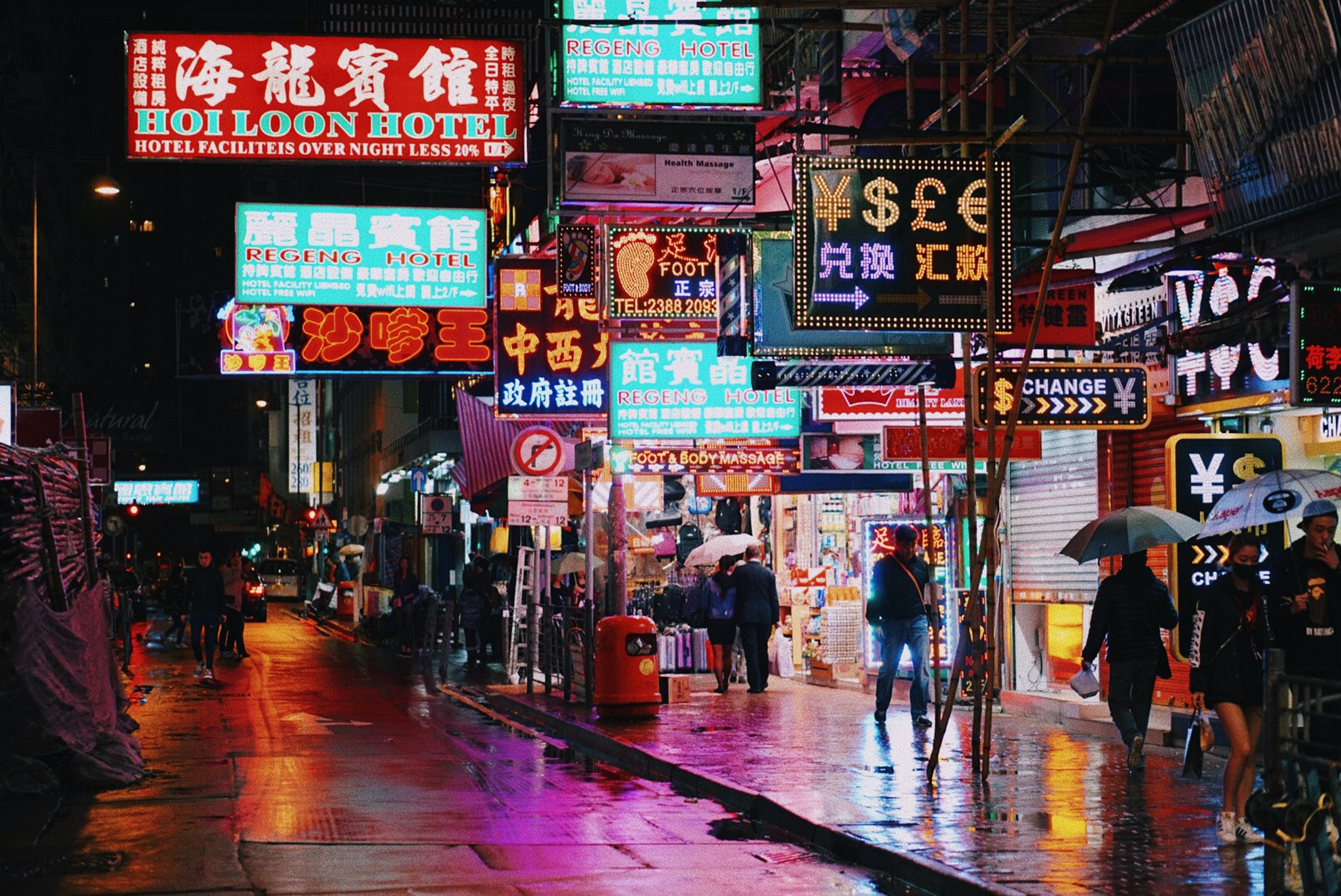 Night time scene of a city street with several neon lights and signs over people walking around with umbrellas in a Hong Kong urban region
