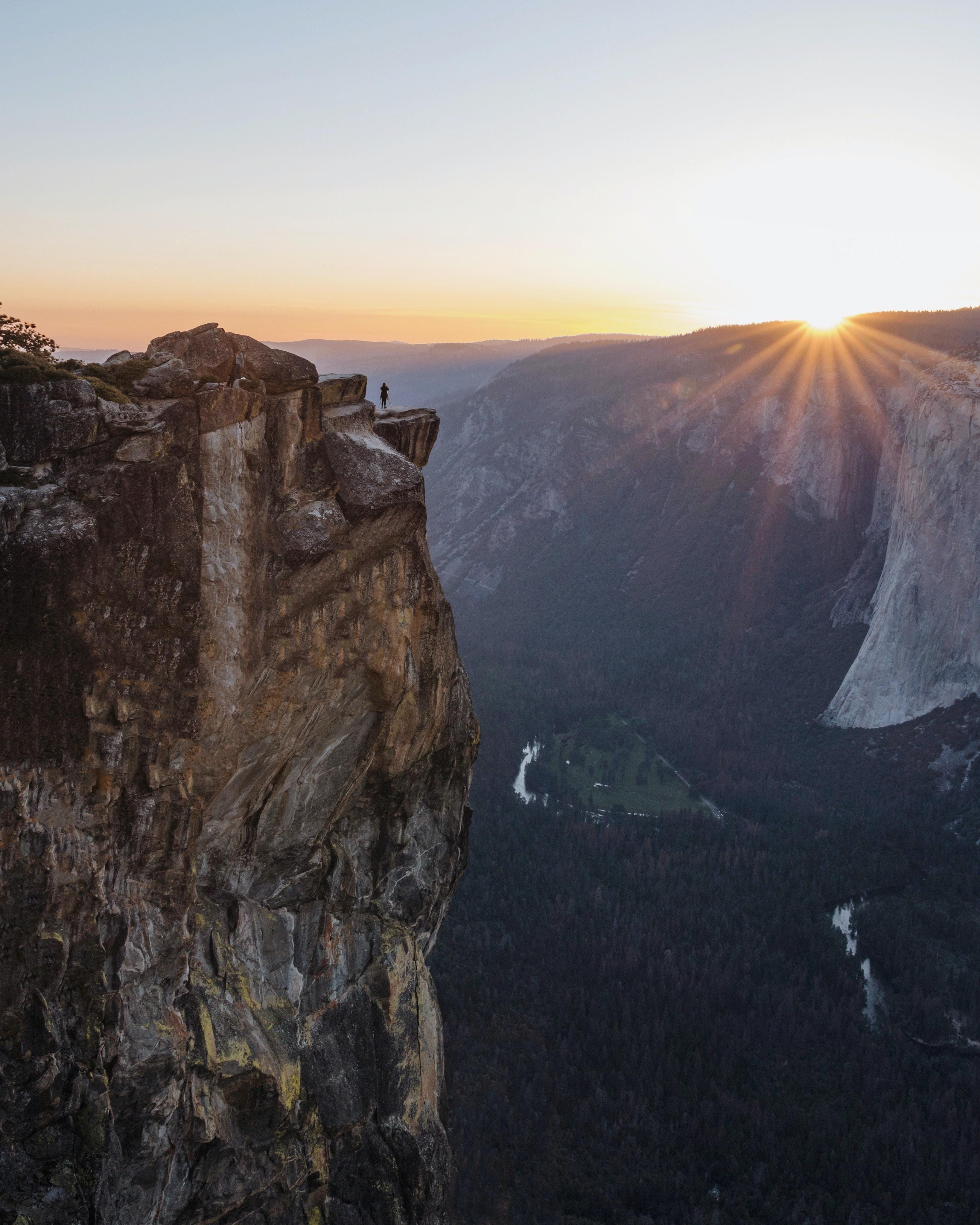 Sun shines on the horizon over a rocky mountain ridge