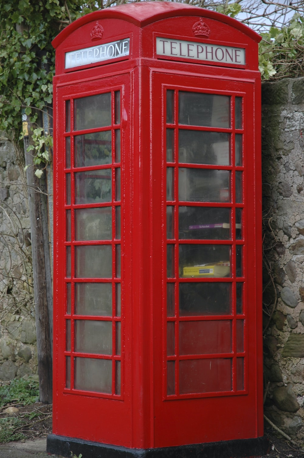 red wooden telephone booth beside gray concrete stonewall at daytime