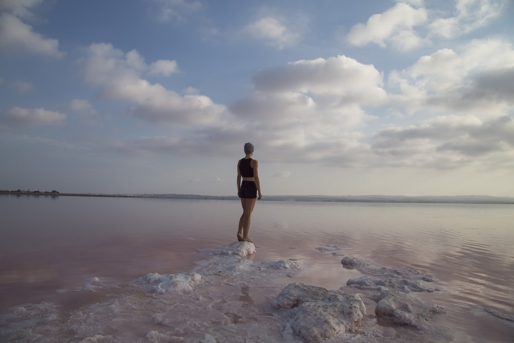 woman standing on top of rock near body of water