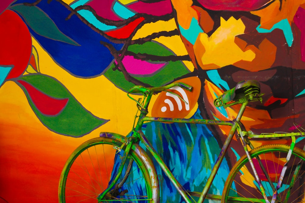 green city bike parked near graffiti art wall