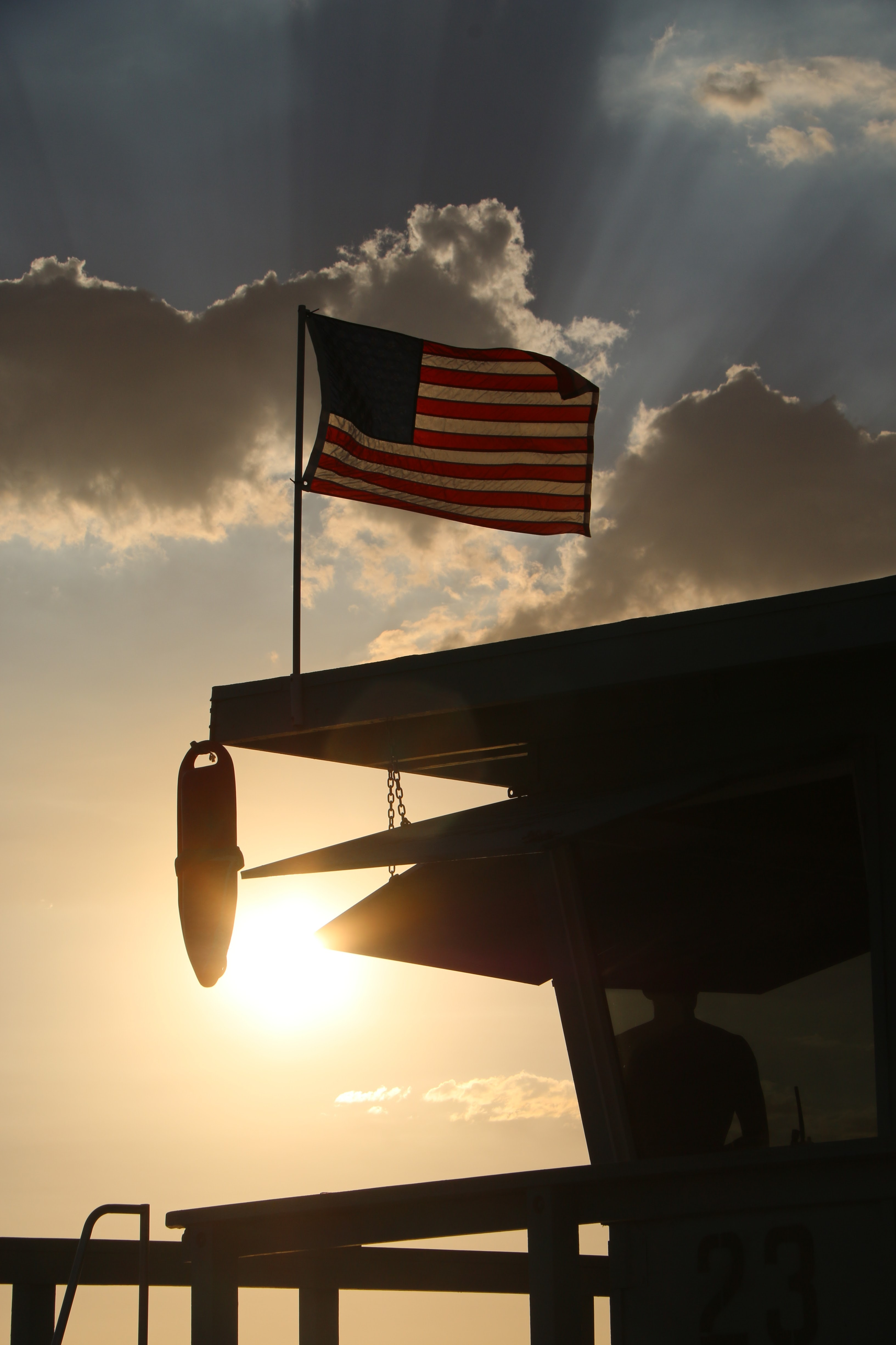 United States flag flying on a rooftop of lifeguard hut at Venice Beach