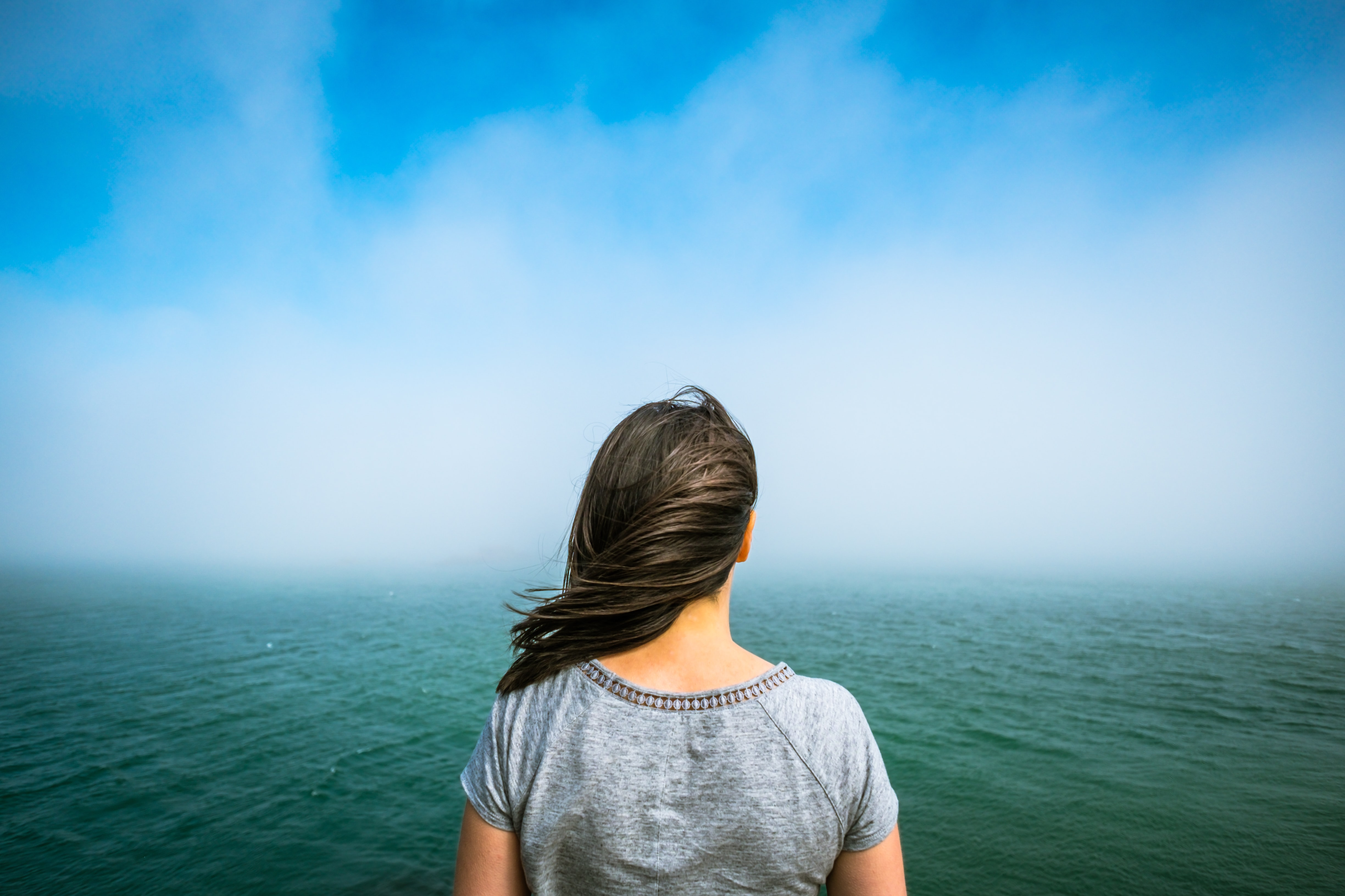 woman looks out at windy ocean view