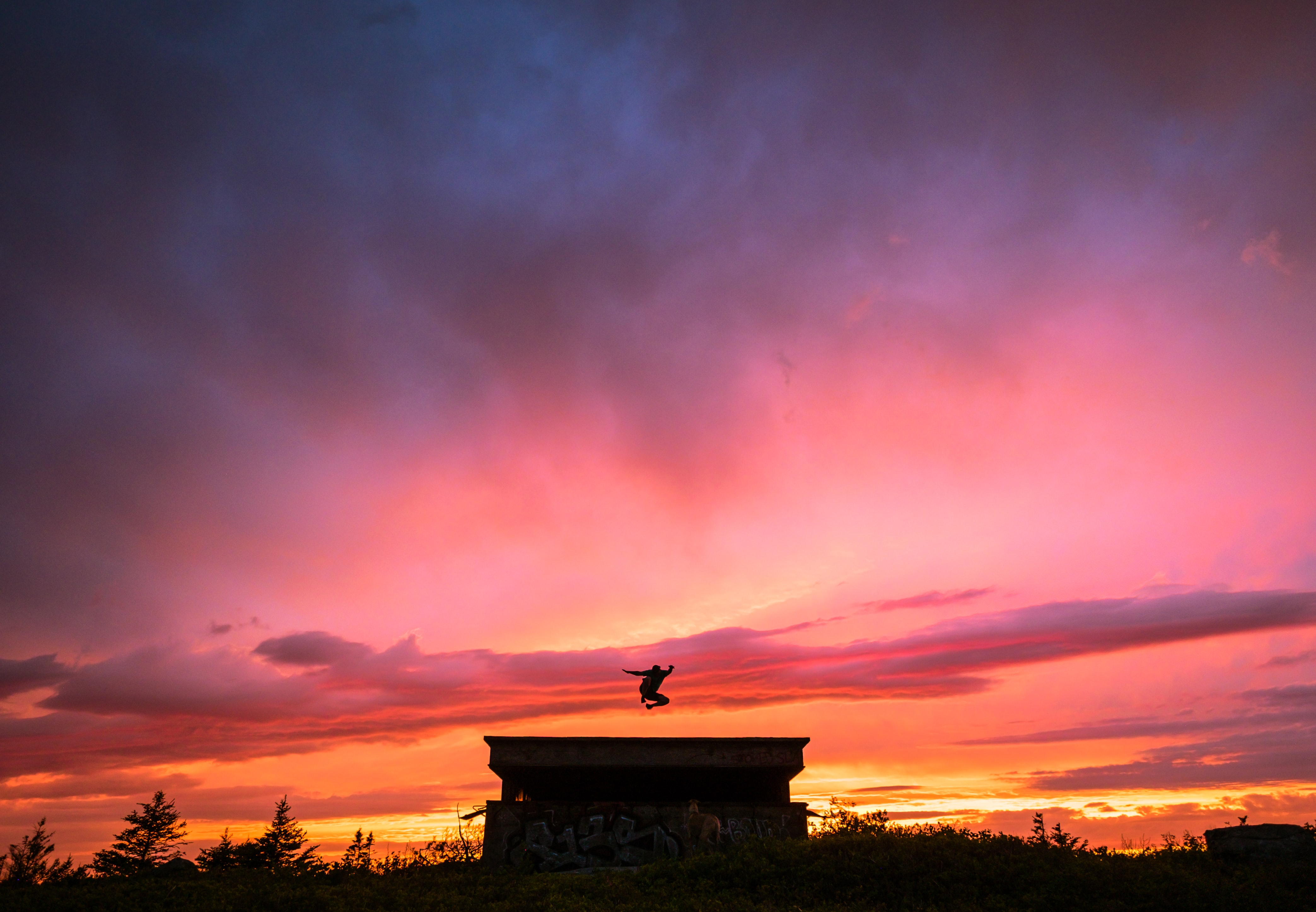 Man jumping from building in Duncan's cove, silhouetted against a fiery sky with pink clouds