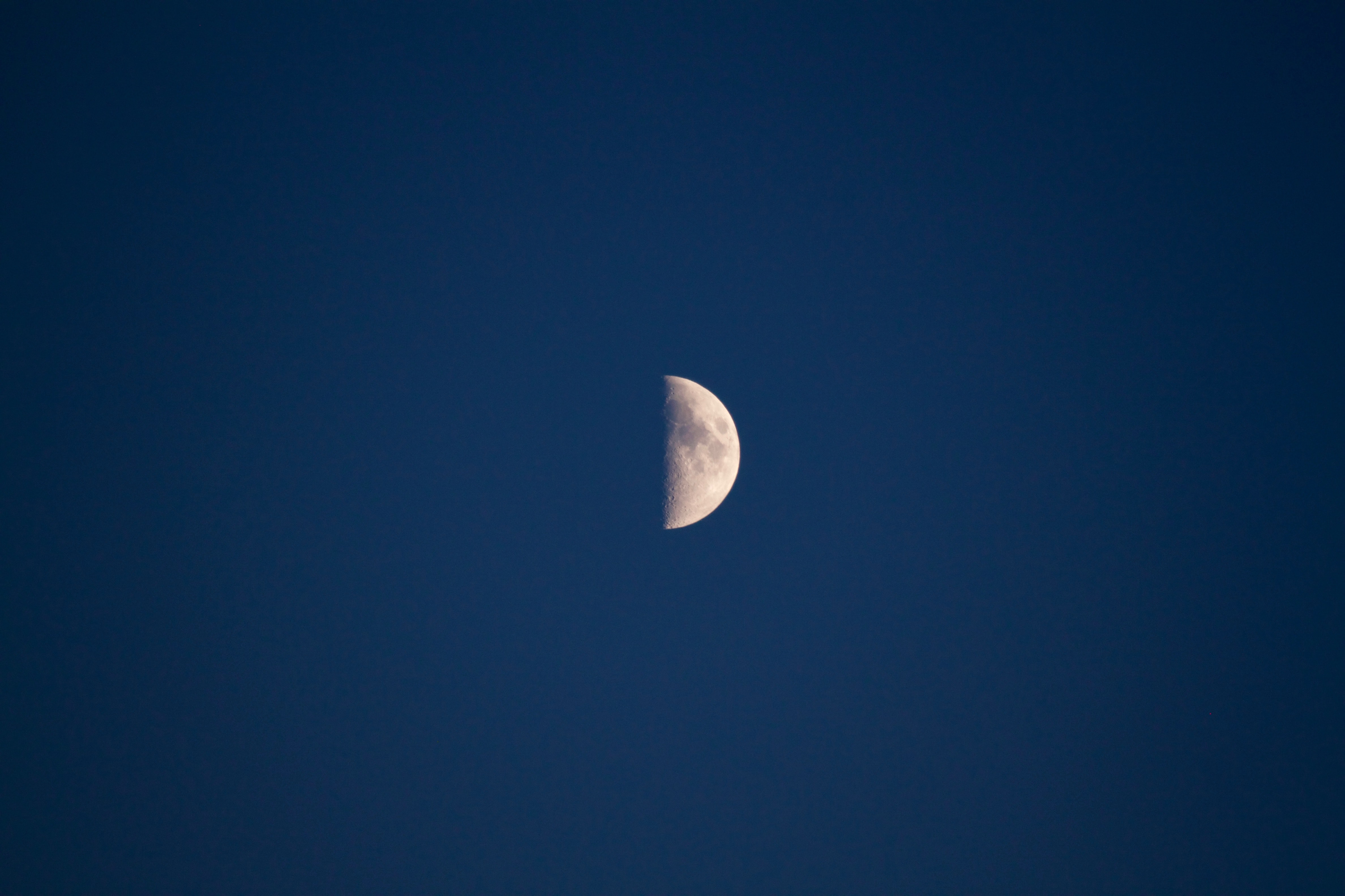 Half moon with visible dark spots in the inky blue sky
