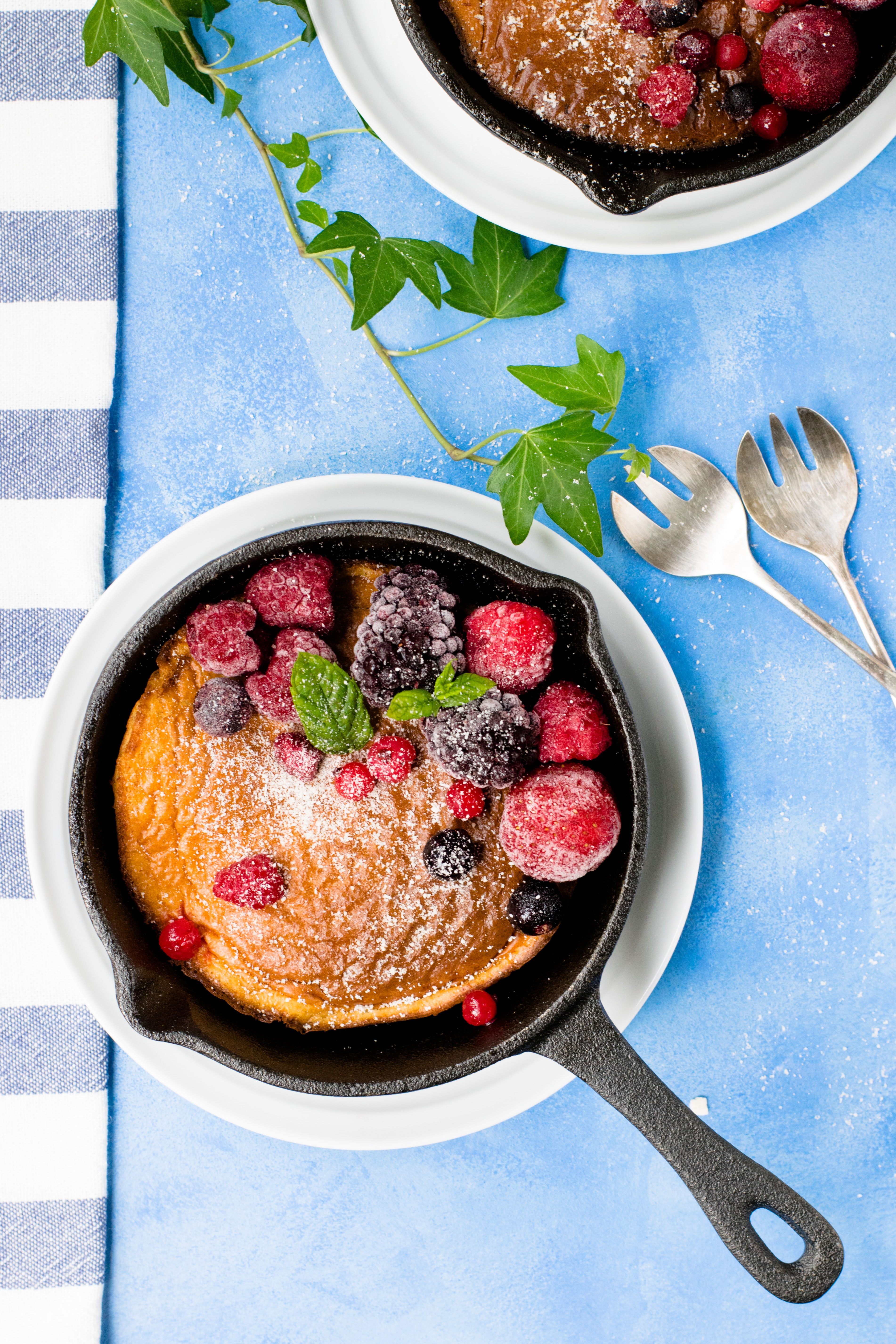 Pancakes in cast iron skillet with berries and blue cloth