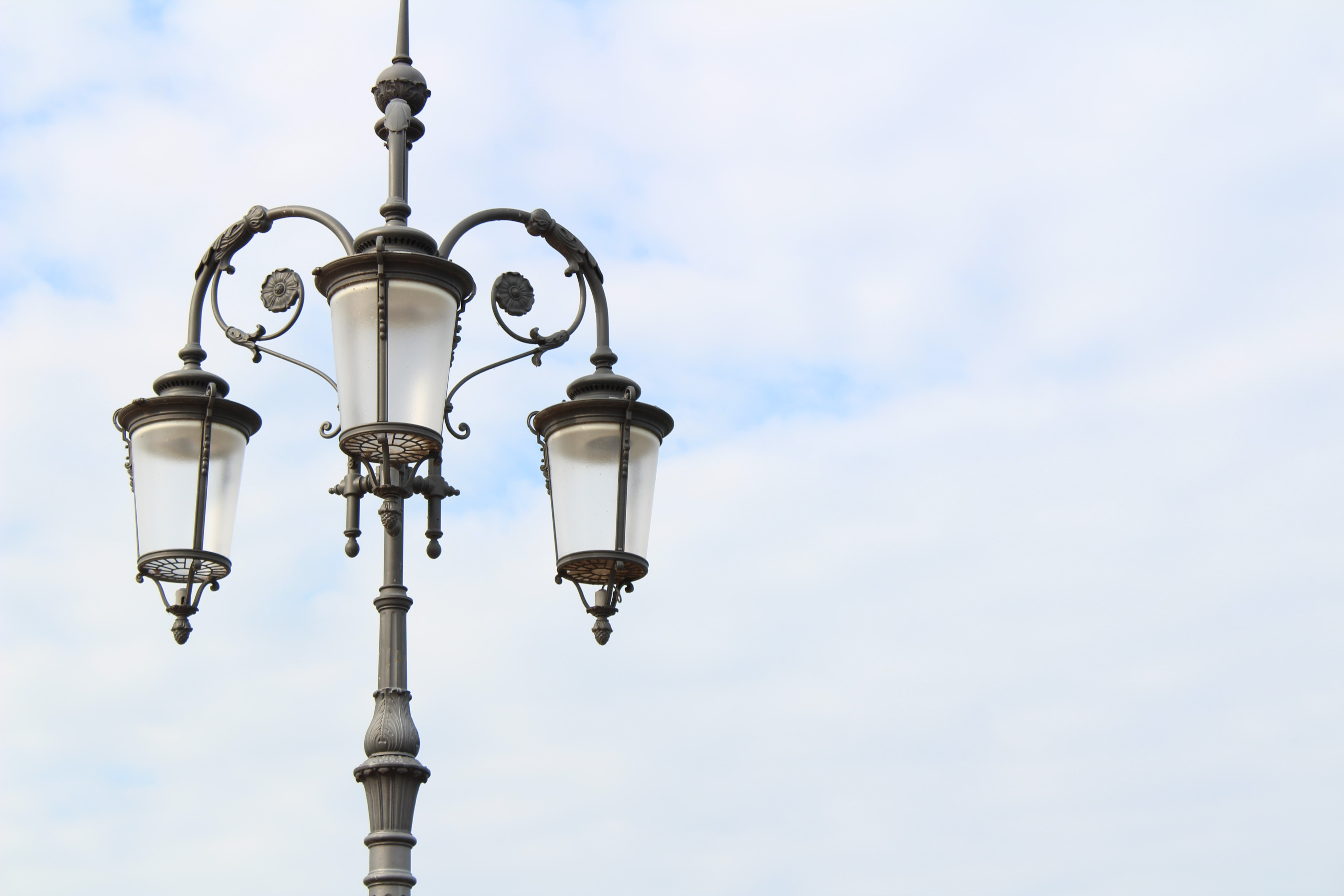 Black lamppost with ornate flower designs and three lanterns against a cloudy sky