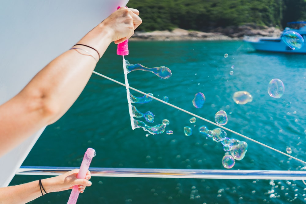person playing with bubbles during daytime