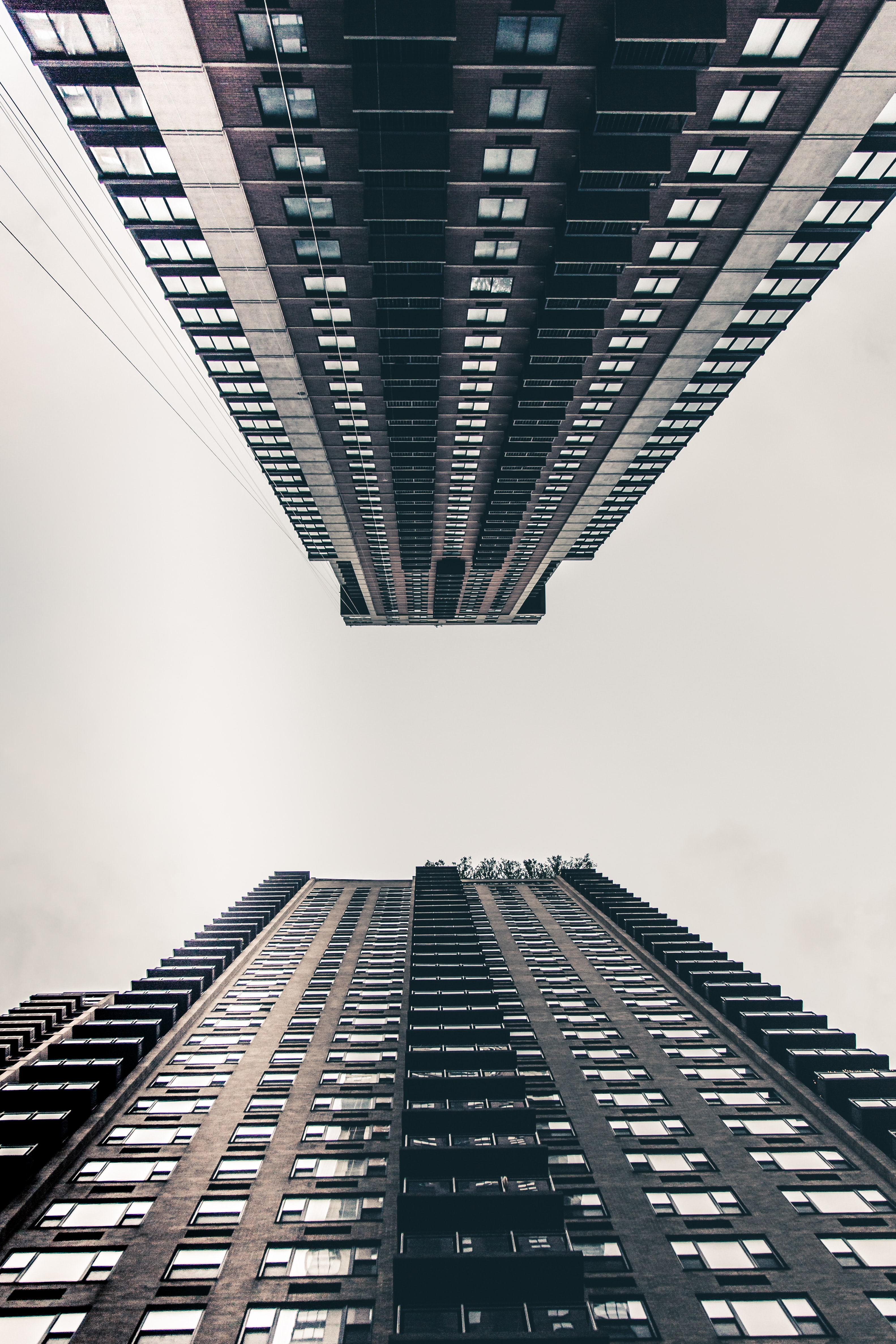 A low-angle shot of two tall apartment buildings in New York under a pale white sky