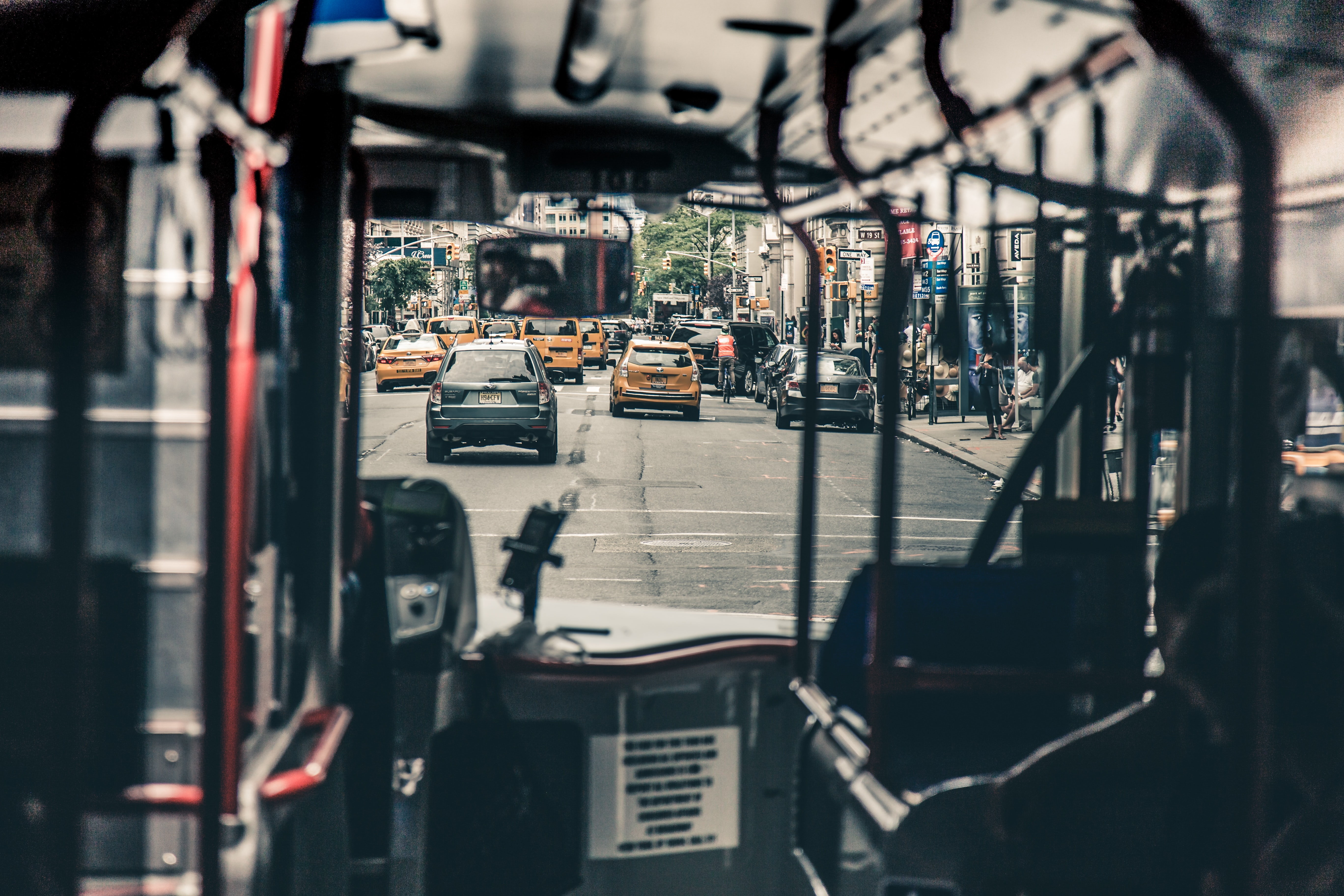 A shot looking through a public bus through the windshield onto a street filled with cars and taxis