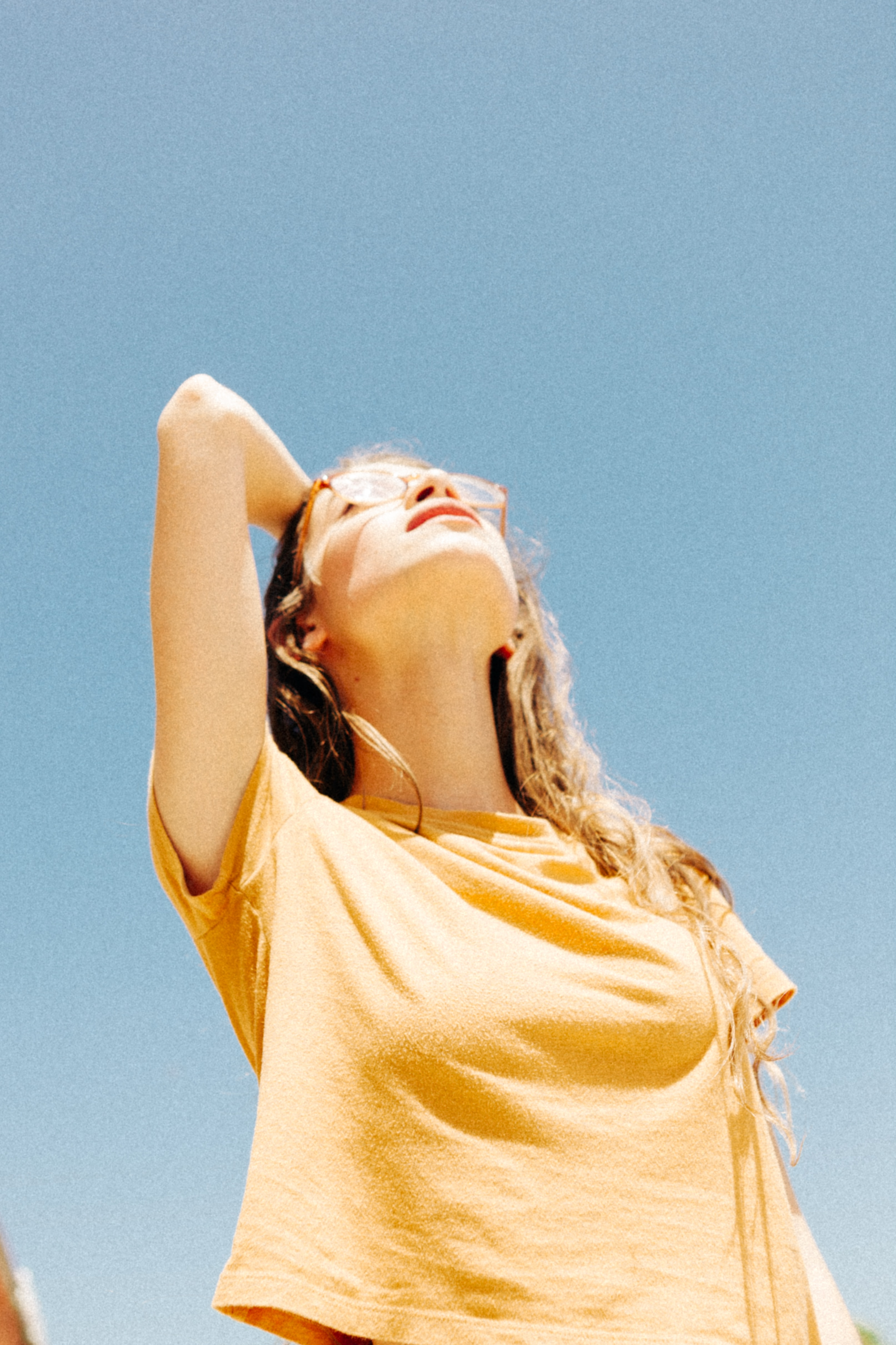 Young woman in a yellow shirt and vintage glasses staring up at the sky