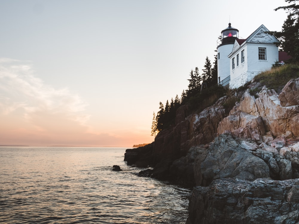 white lighthouse near sea at daytime