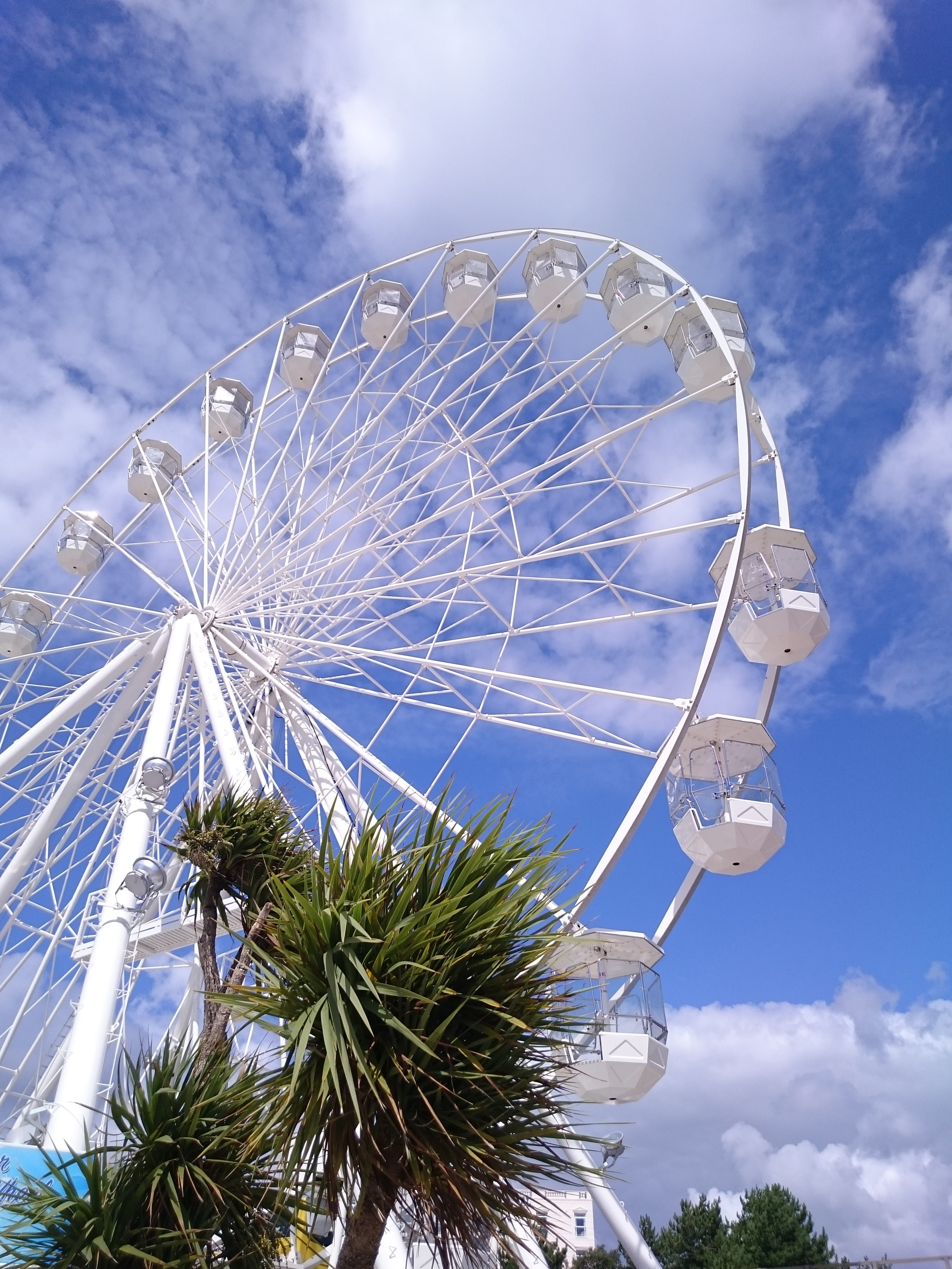 A white Ferris wheel under the bright cloudy sky in Bournemouth.