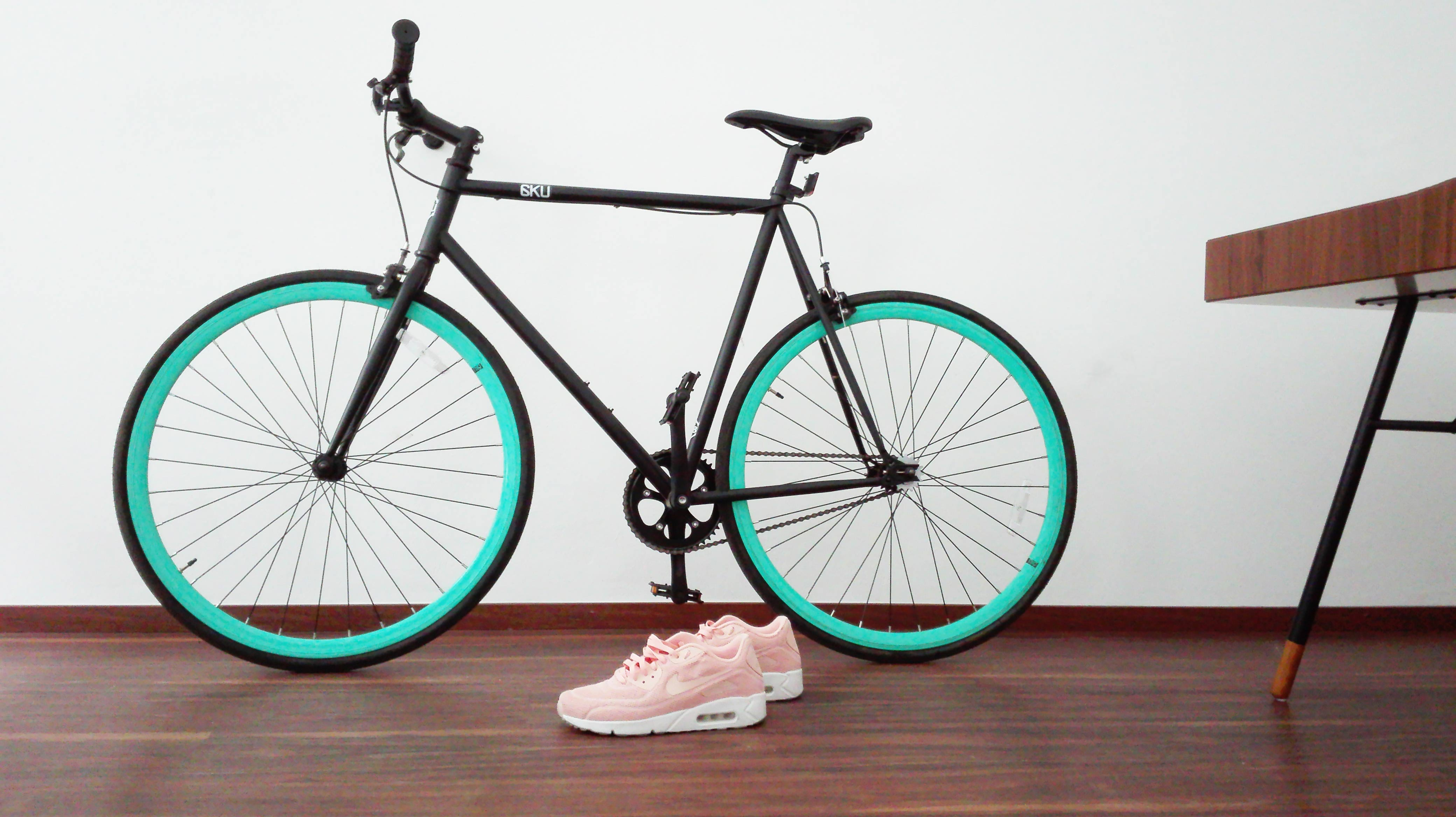 A black road bicycle and a pair of pink sneakers on wooden floor in a room