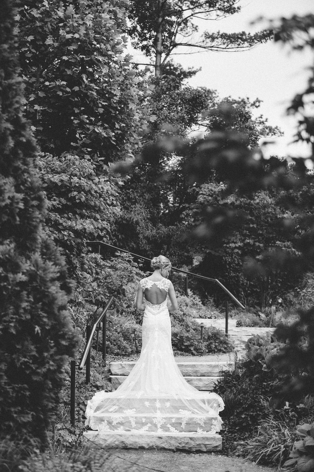 woman in white bridal gown walking on gray concrete stair