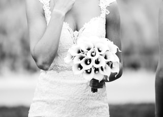 greyscale photography of woman holding bouquet