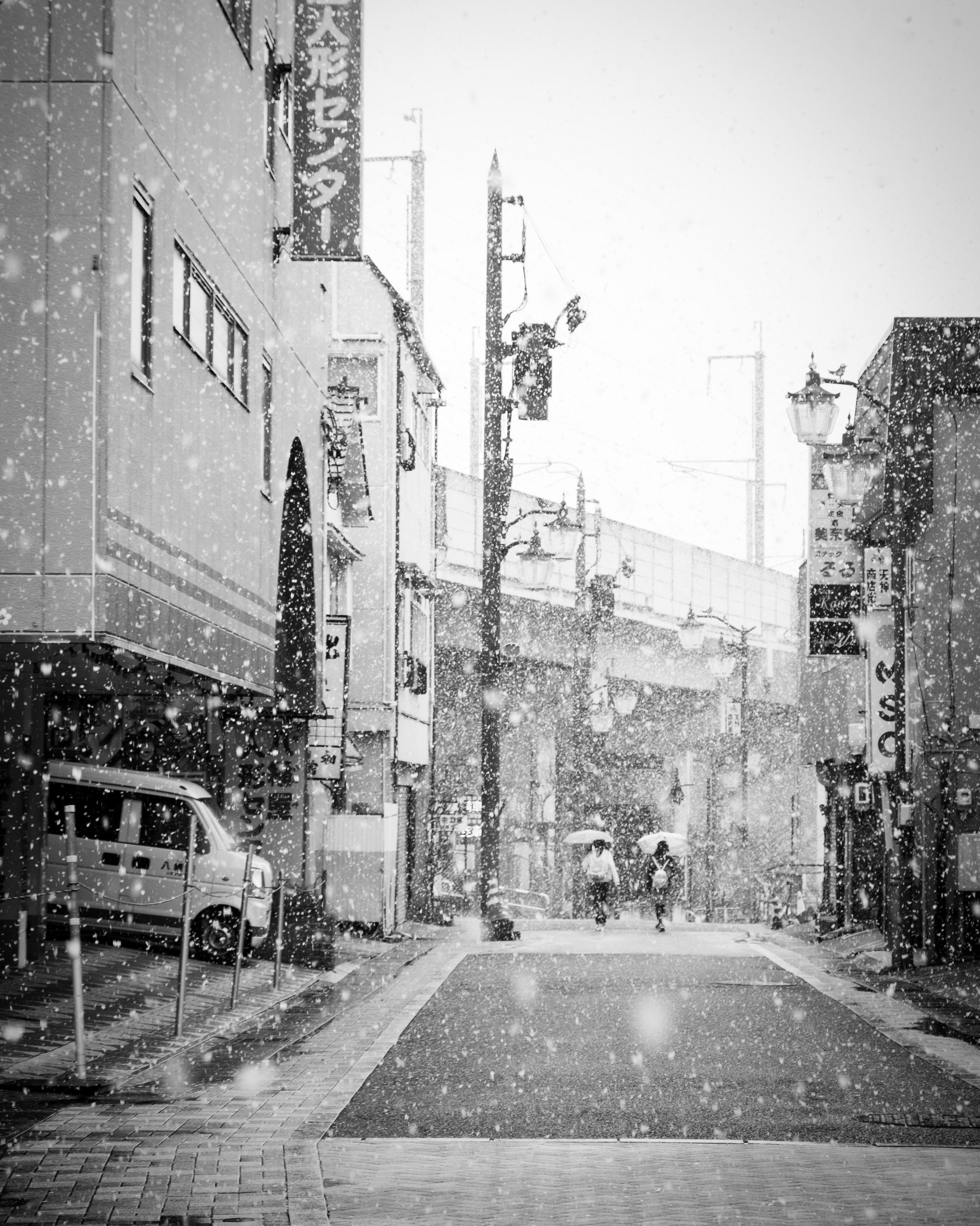 Black and white shot of city street in daytime with snow in Ueda