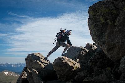 photo of man climbing mountain hiking teams background