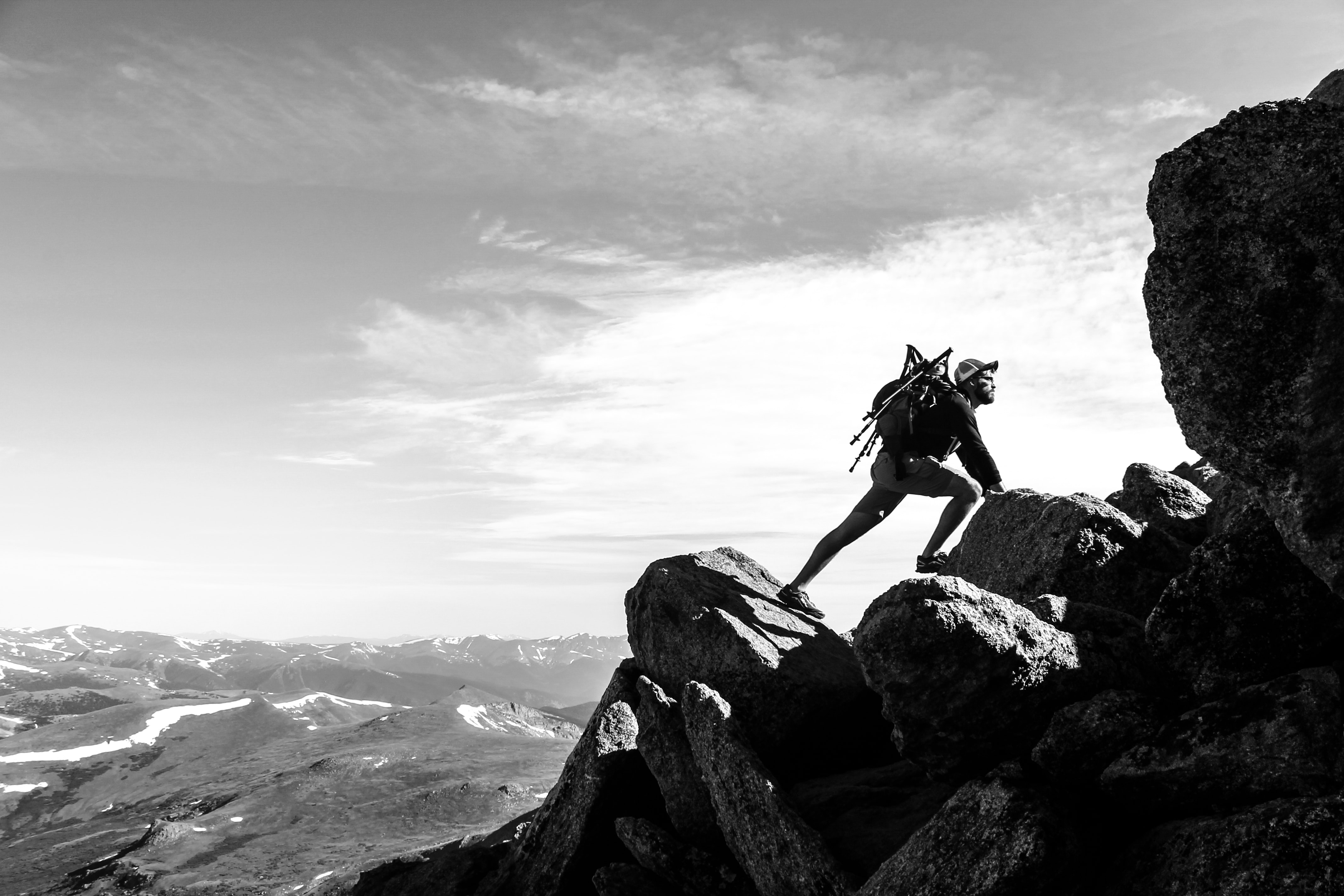 A black-and-white shot of a male rock climber against the mountain landscape.