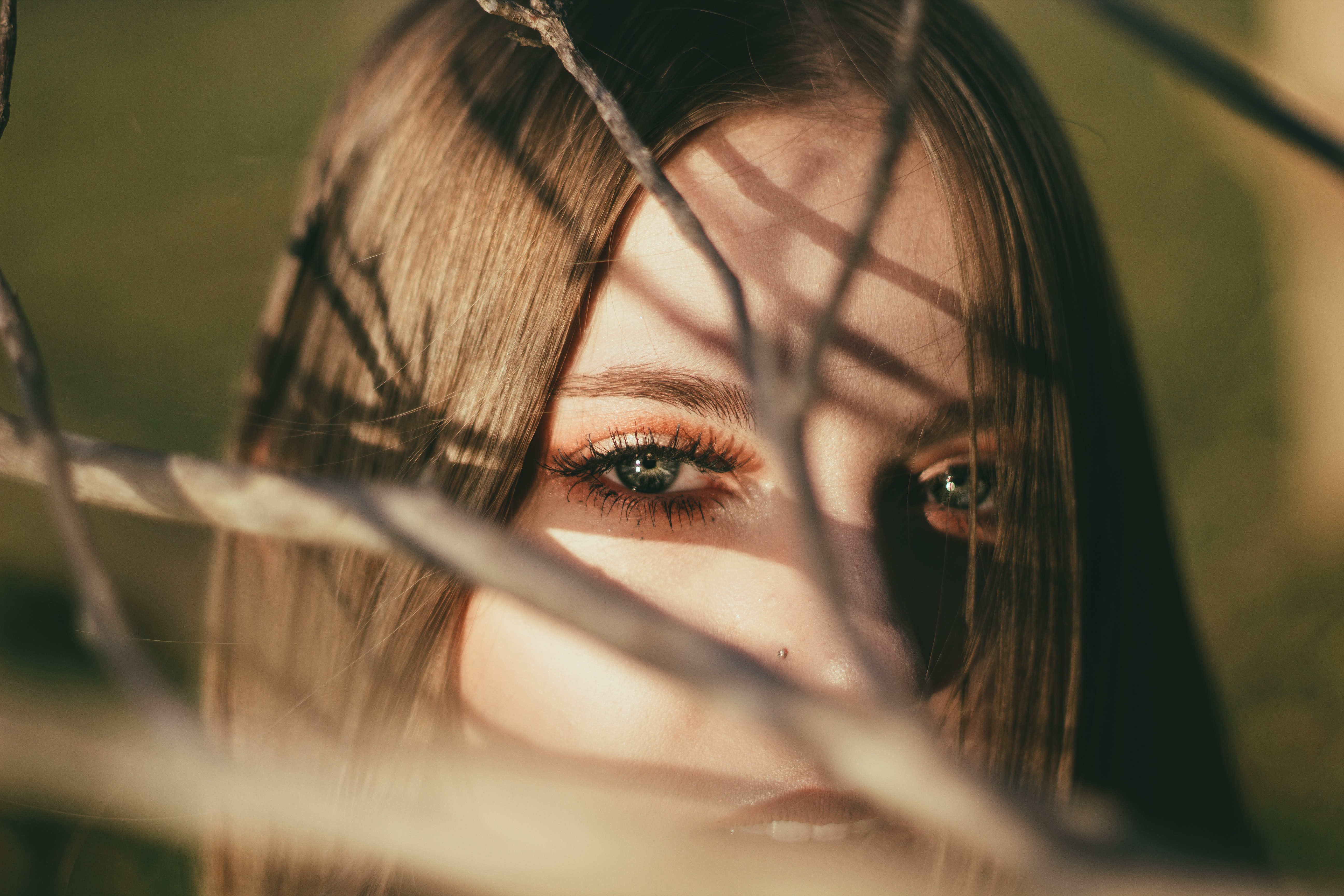 Woman with dramatic makeup peer through branches