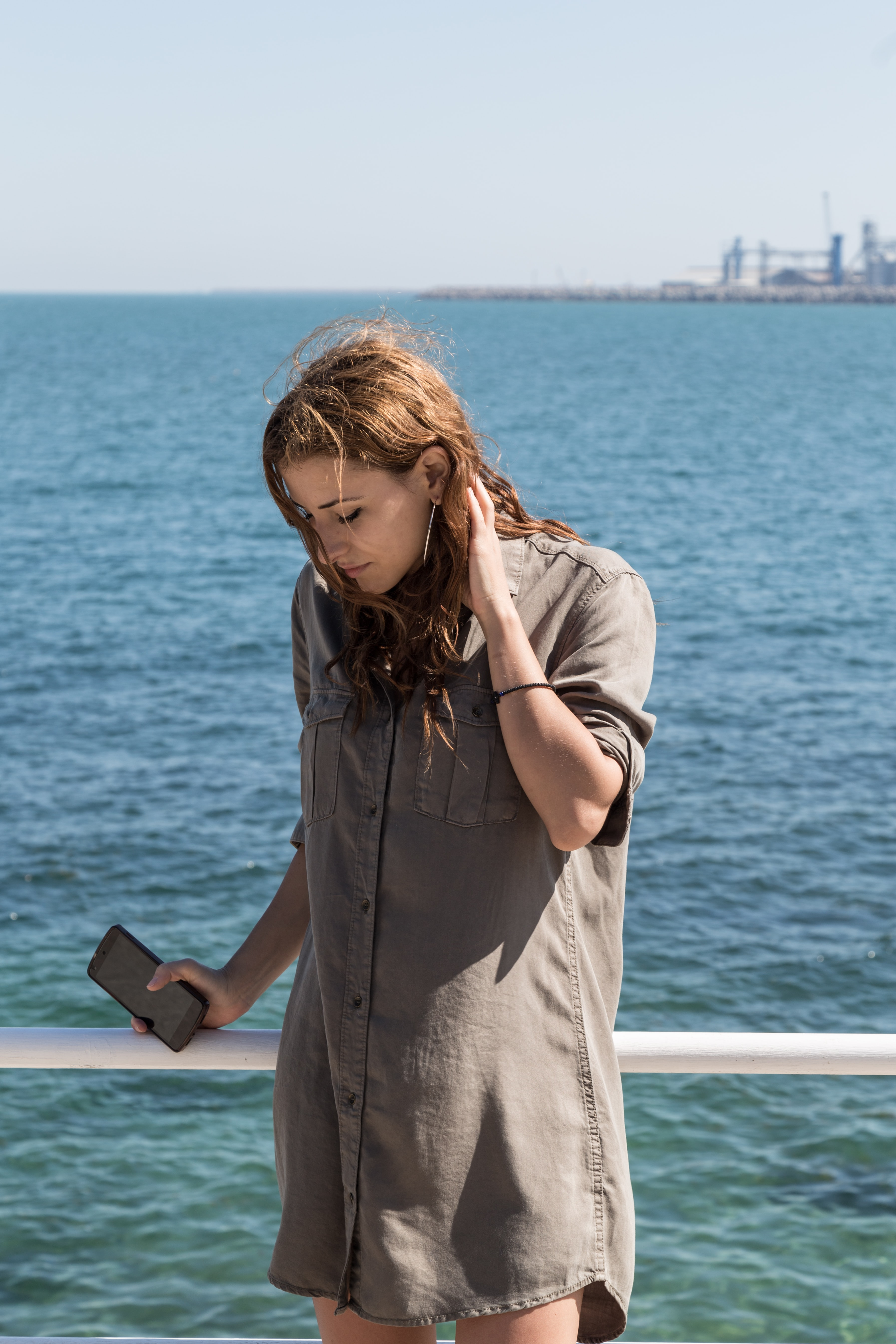 Woman on an ocean ferry holding a smartphone and her hair