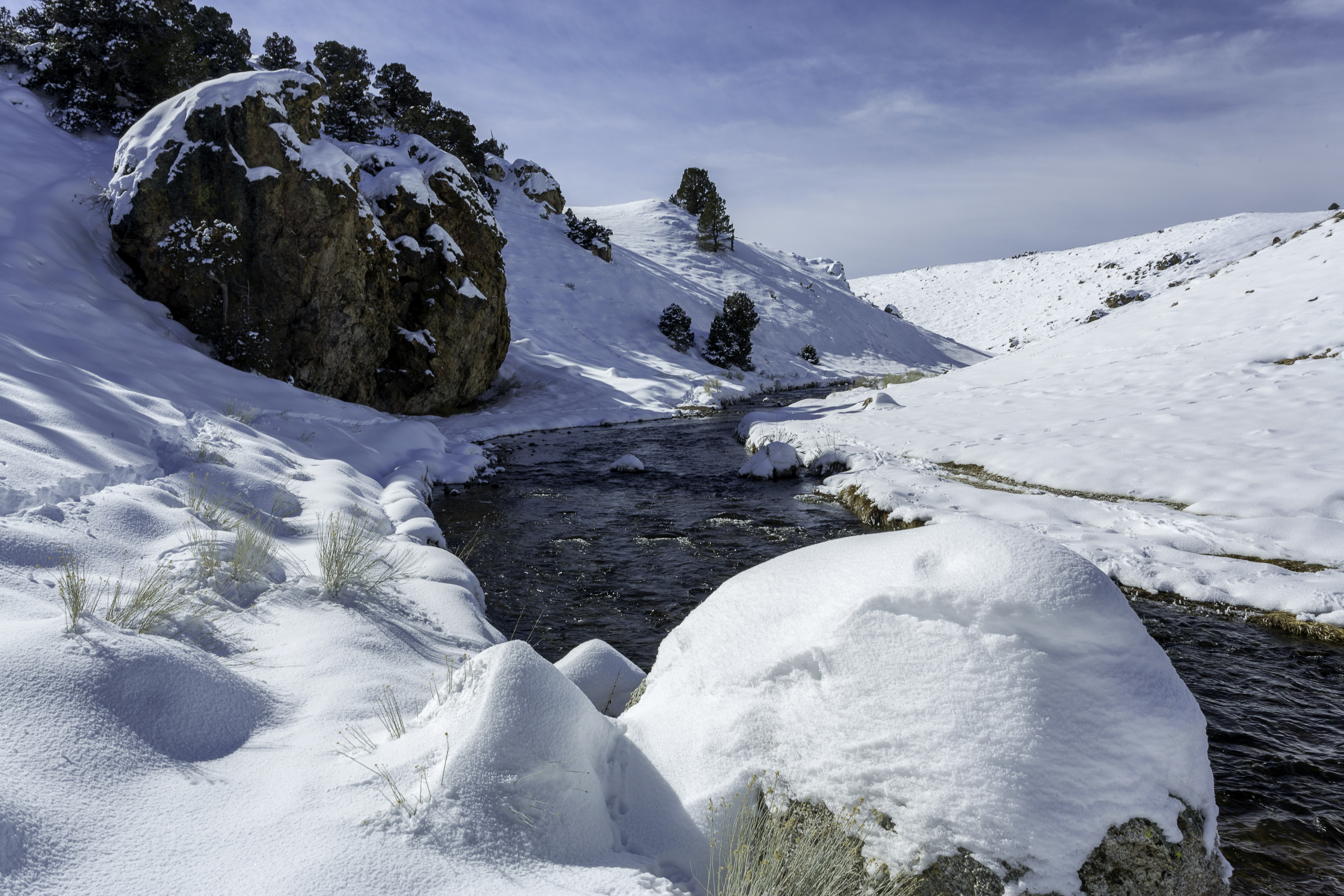 An icy stream rushes past a snowy winter landscape