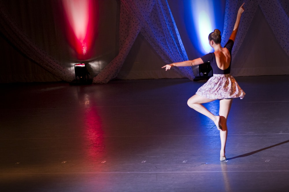 ballerina on stage with red and blue spotlights
