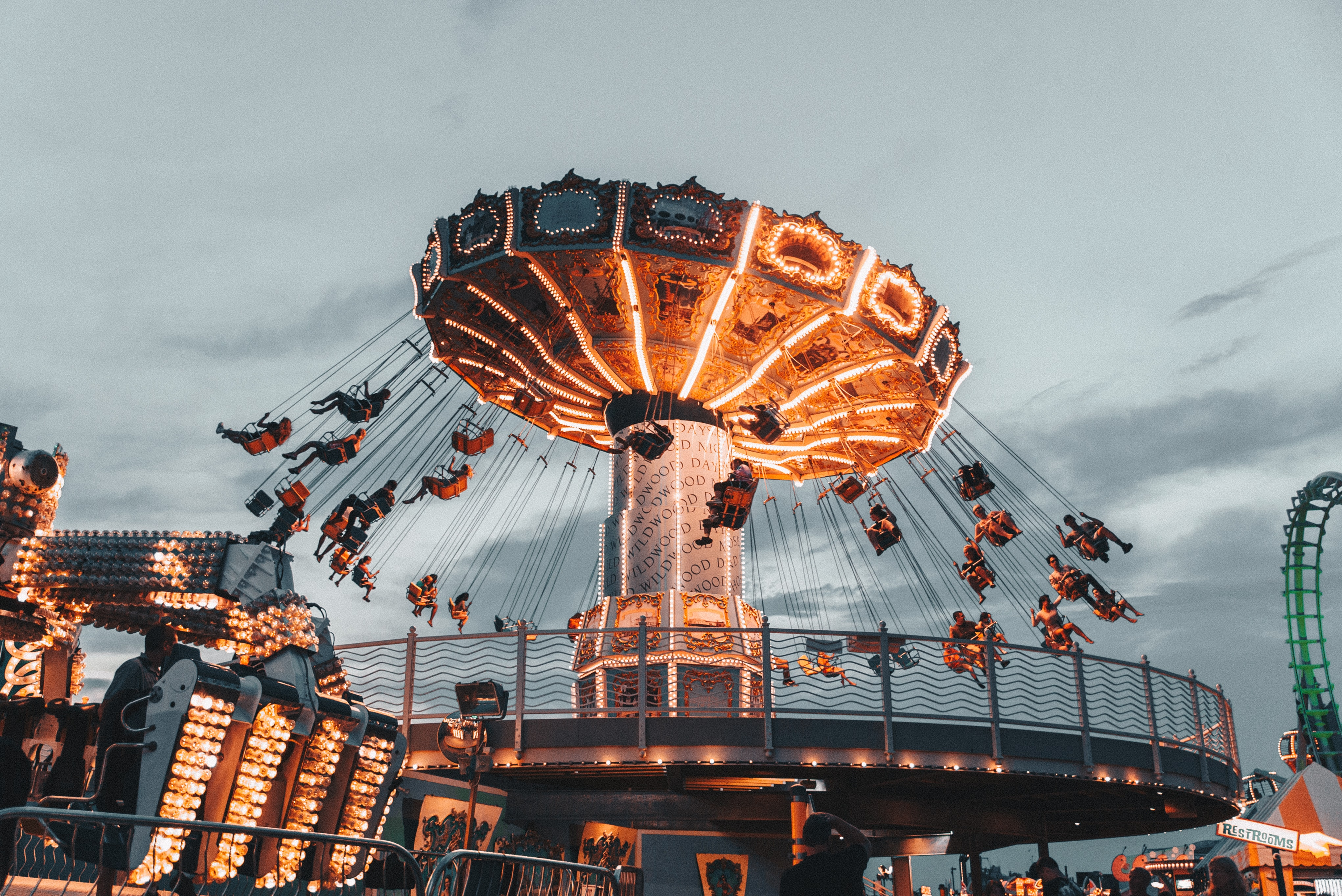 Wildwood fairgoers suspended in the air on an operating swing ride as others watch on