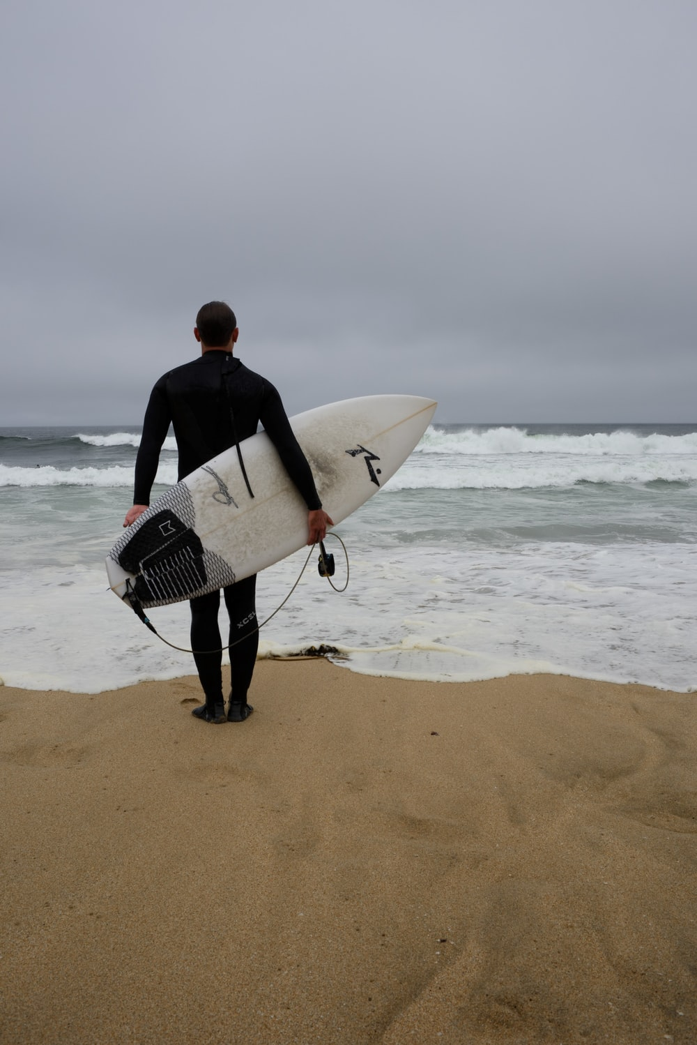 man in black suit holding white surfboard walking on beach during daytime