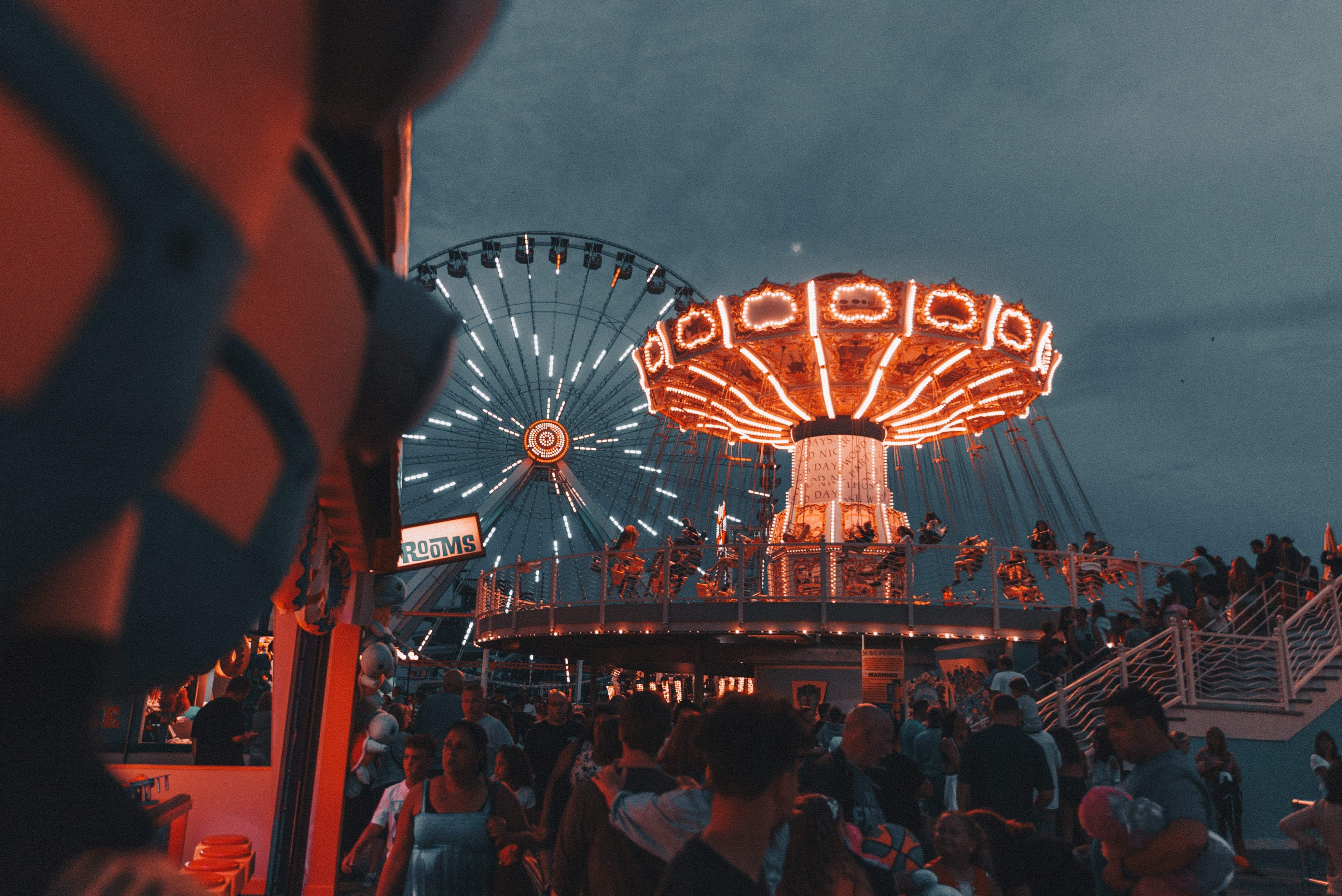 Crowd enjoying Wildwood boardwalk amusement park with swing ride and Ferris Wheel glowing in the night