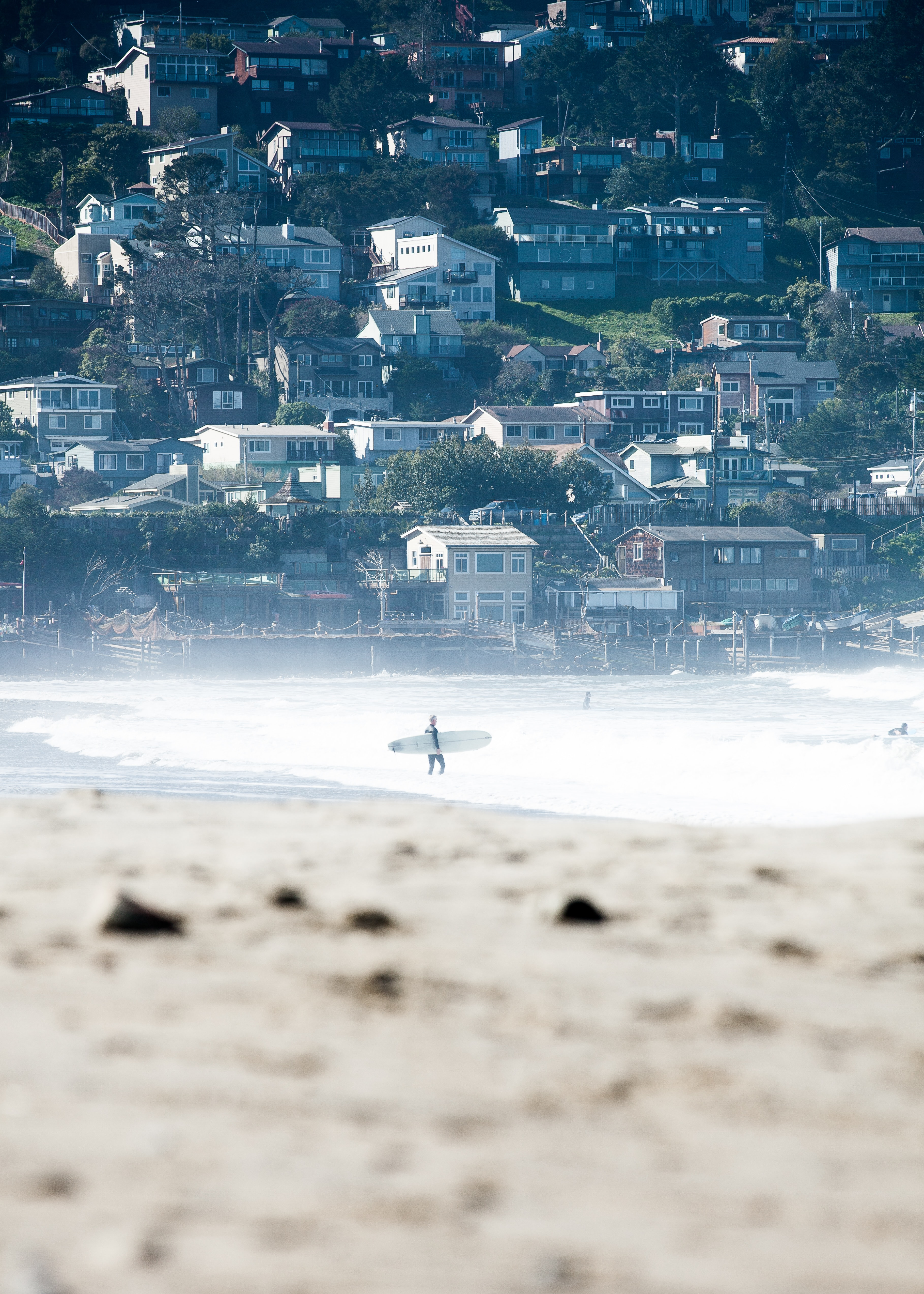 Surfer entering the water near the shoreline town at Pacifica State Beach
