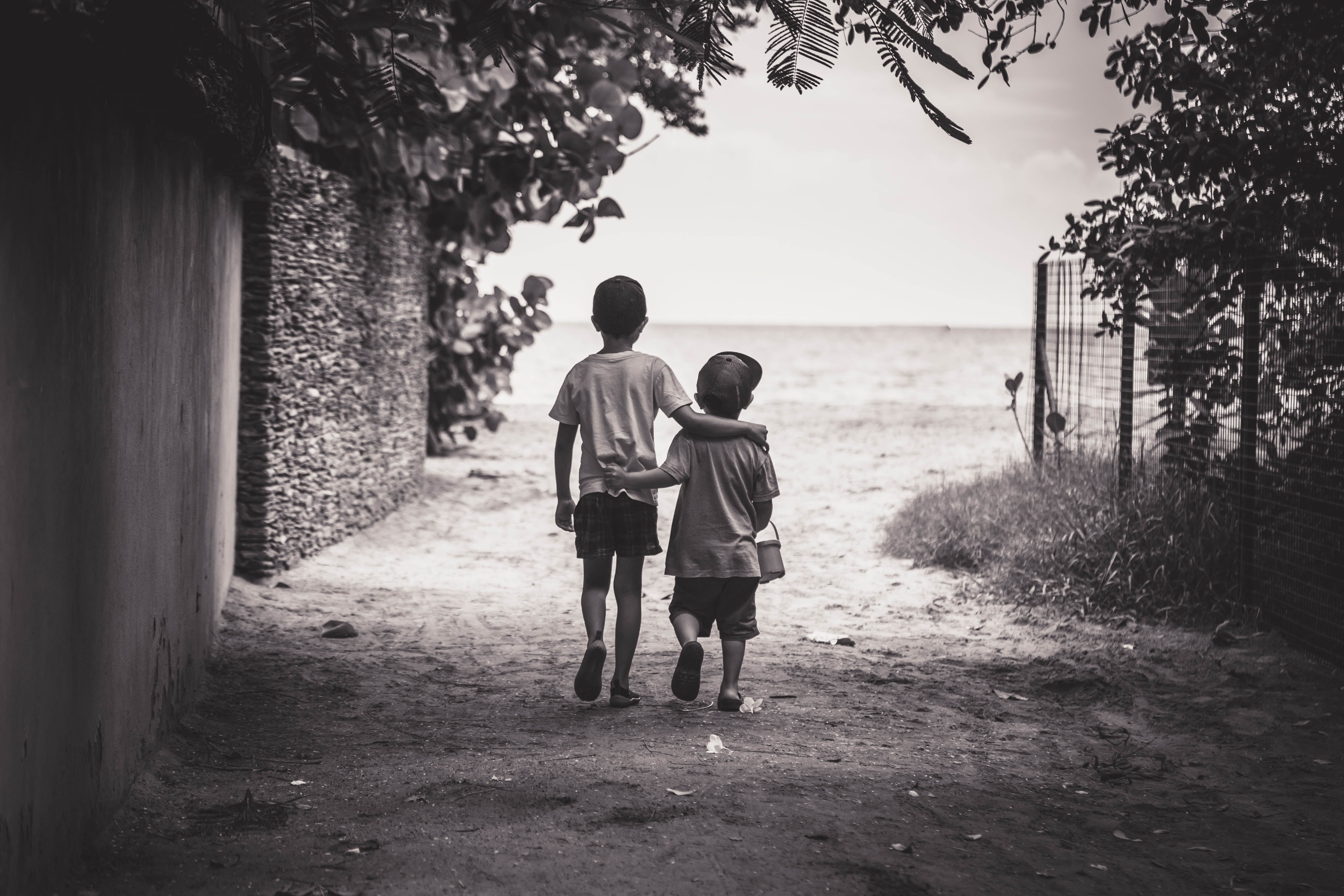 grayscale photography of child and toddler while walking