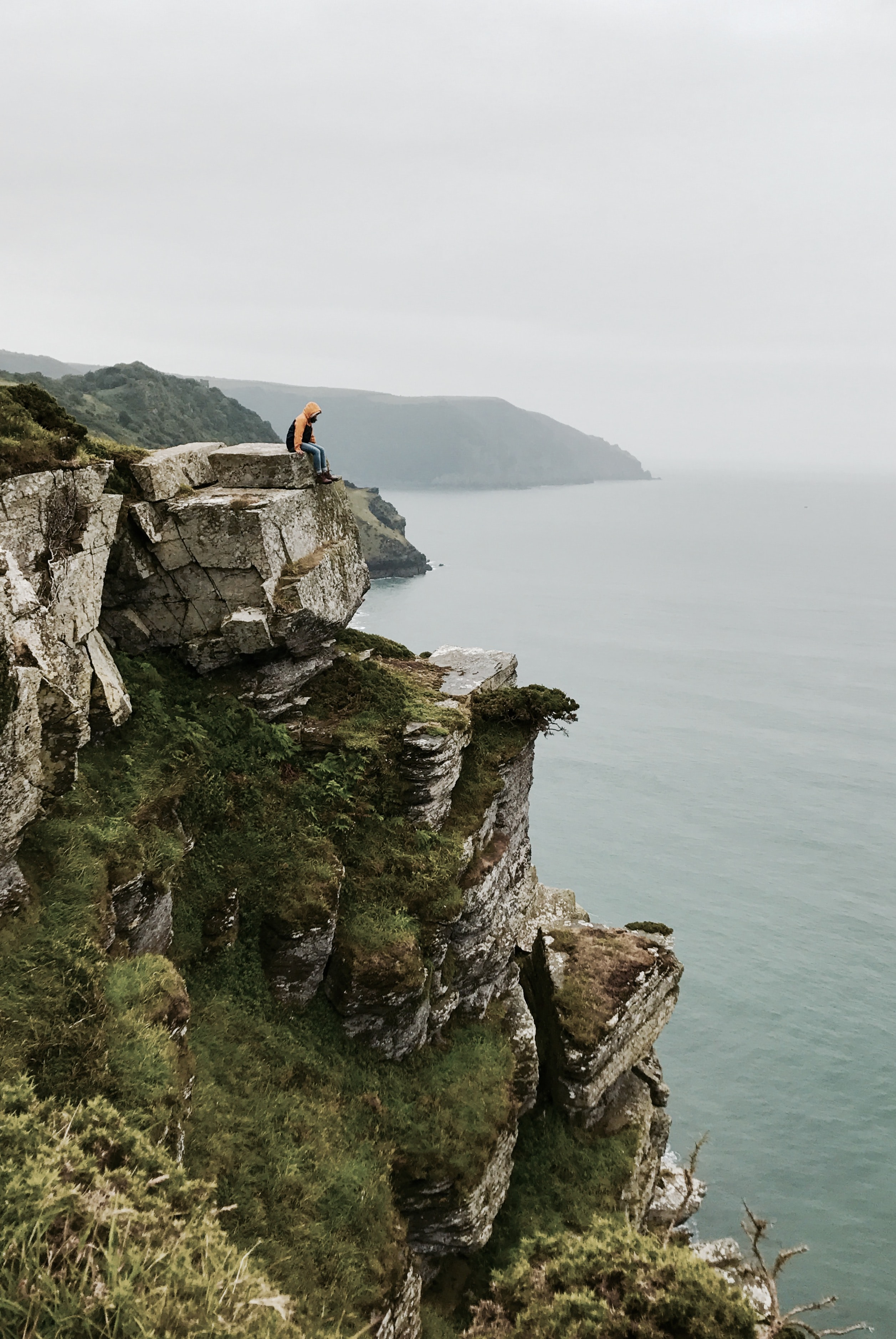 person sitting on cliffside during daytime