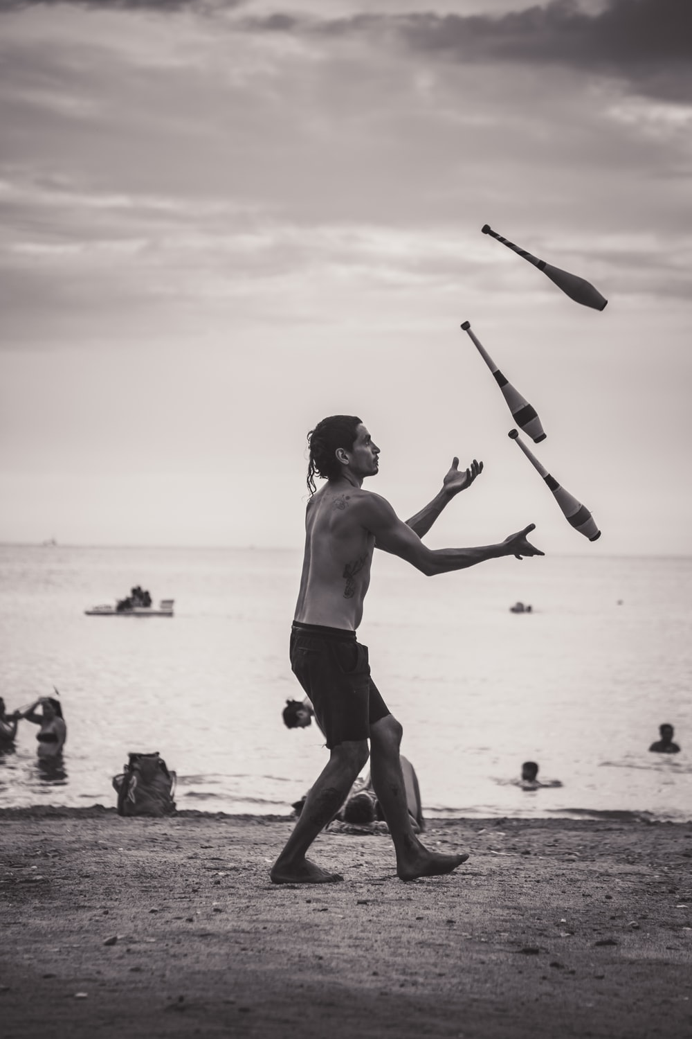 grayscale photo of man juggling on shore