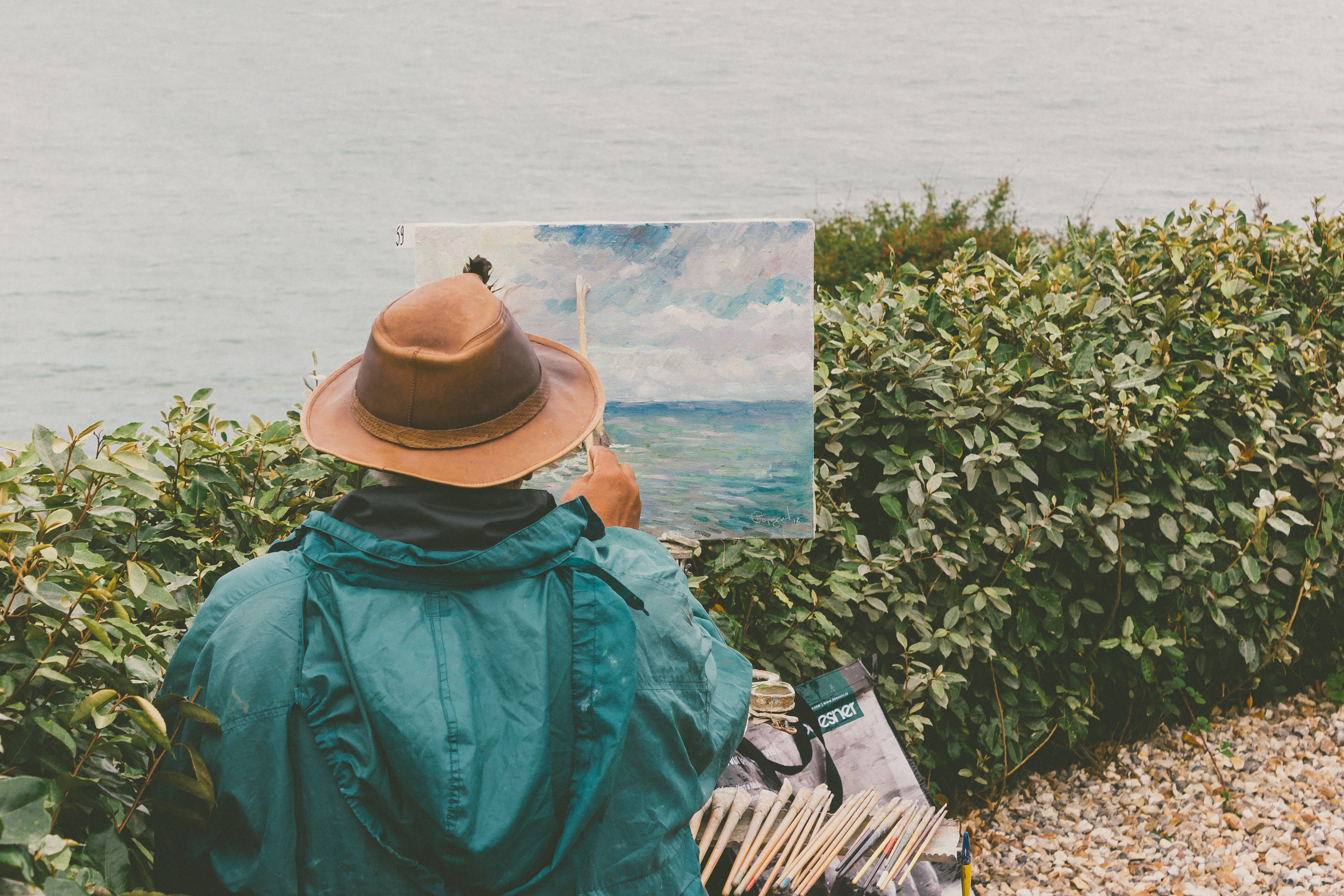 Artist painting water and sky while sitting near the lake